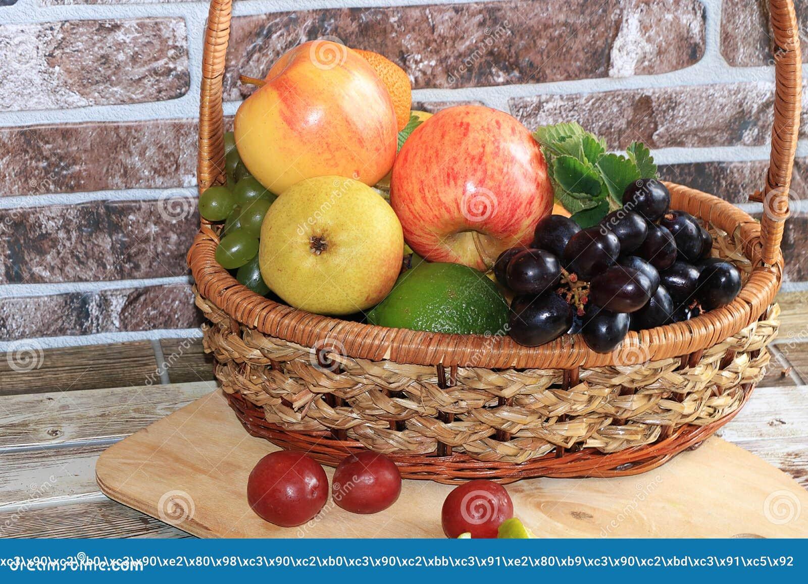Raisins et pommes noirs juteux dans un panier avec le plan rapproché de baisses,