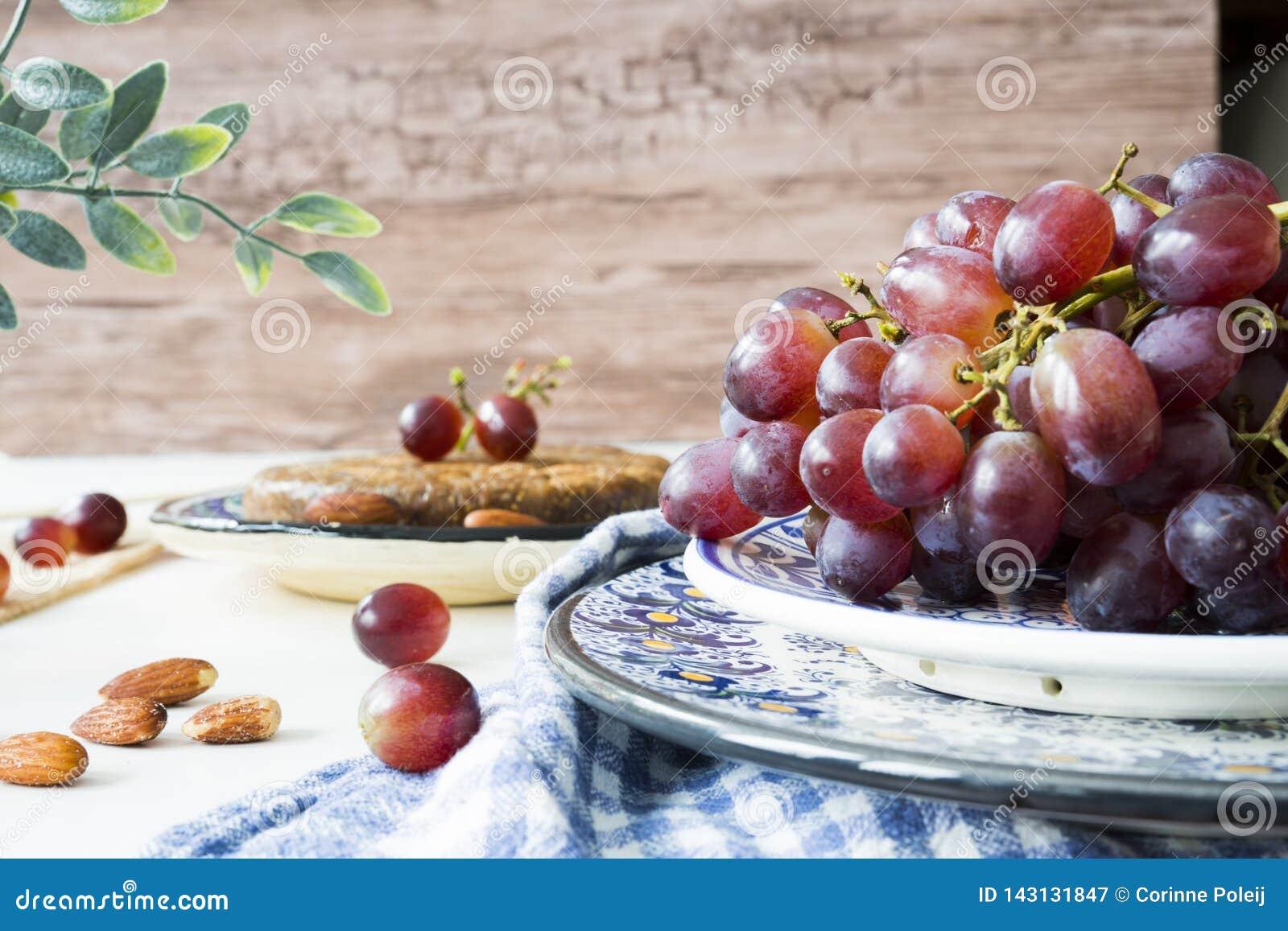 Raisins rouges de groupe dans la cuvette bleue, sur le fond en bois