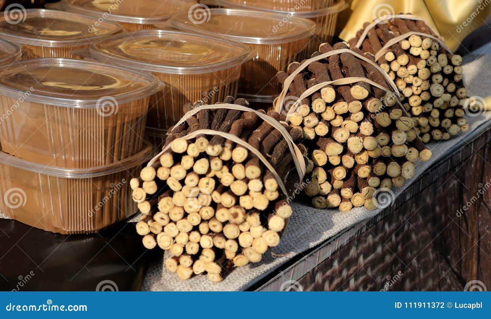 Raizes de alcaçuz amarradas e recipientes transparentes do extrato de alcaçuz Prateleira dedicada em um mercado local