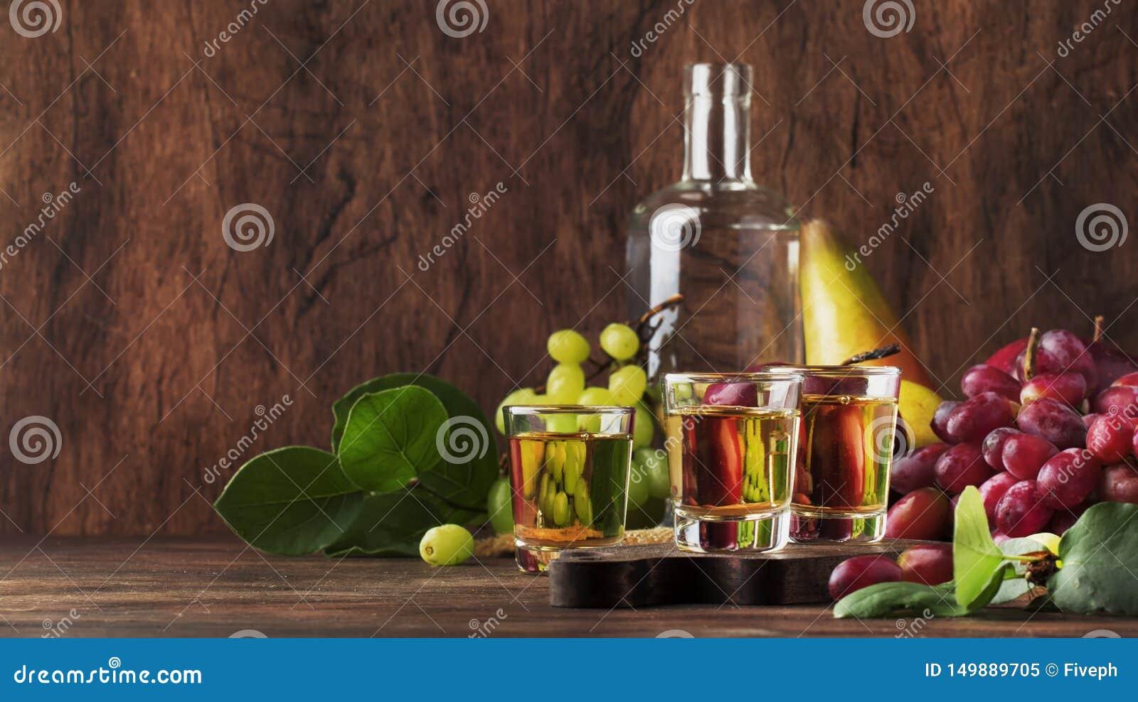 Rakija, raki o rakia - tipo fuerte balcánico basado en las frutas fermentadas, tabla de madera del vintage, aún vida del brandy d