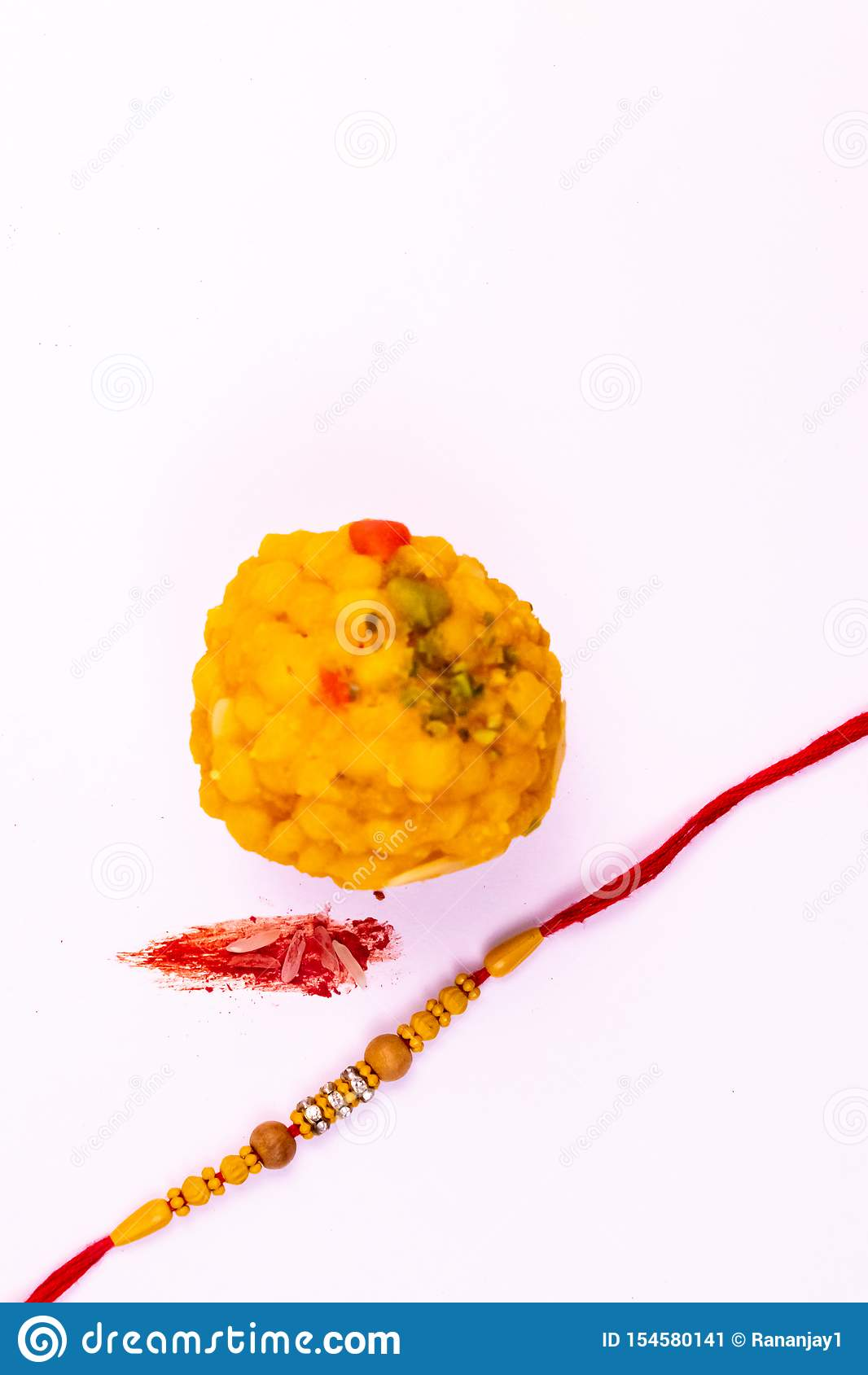 Raksha Bandhan Festival – Dichte mening van elegante Rakhi, snoepjes, blauw giftvakje, en Indische muntnota s met kumkum en rijst