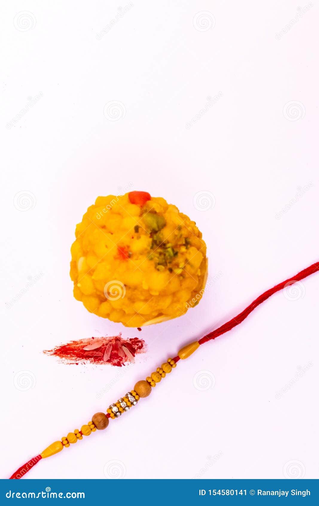 Raksha Bandhan Festival – ideia próxima de Rakhi elegante, de doces, da caixa de presente azul, e de notas indianas da moeda com