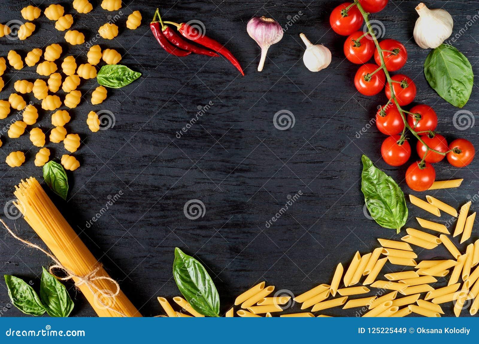 Ram av italiensk traditionell mat, kryddor och ingredienser för att laga mat som basilika, körsbärsröda tomater, chilipeppar, vit