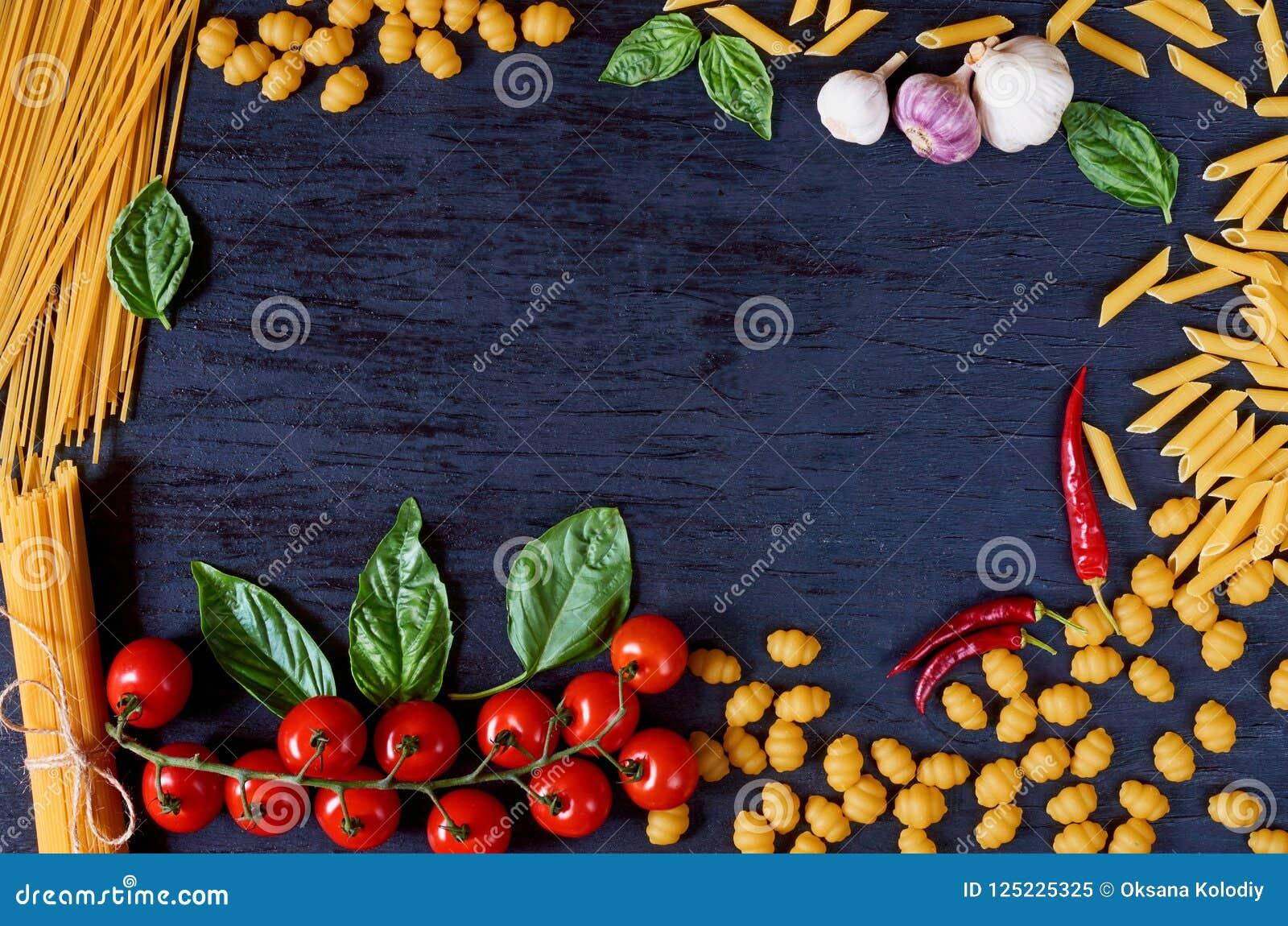 Ram av italiensk traditionell mat, kryddor och ingredienser för att laga mat som basilika, körsbärsröda tomater, vitlök och olik