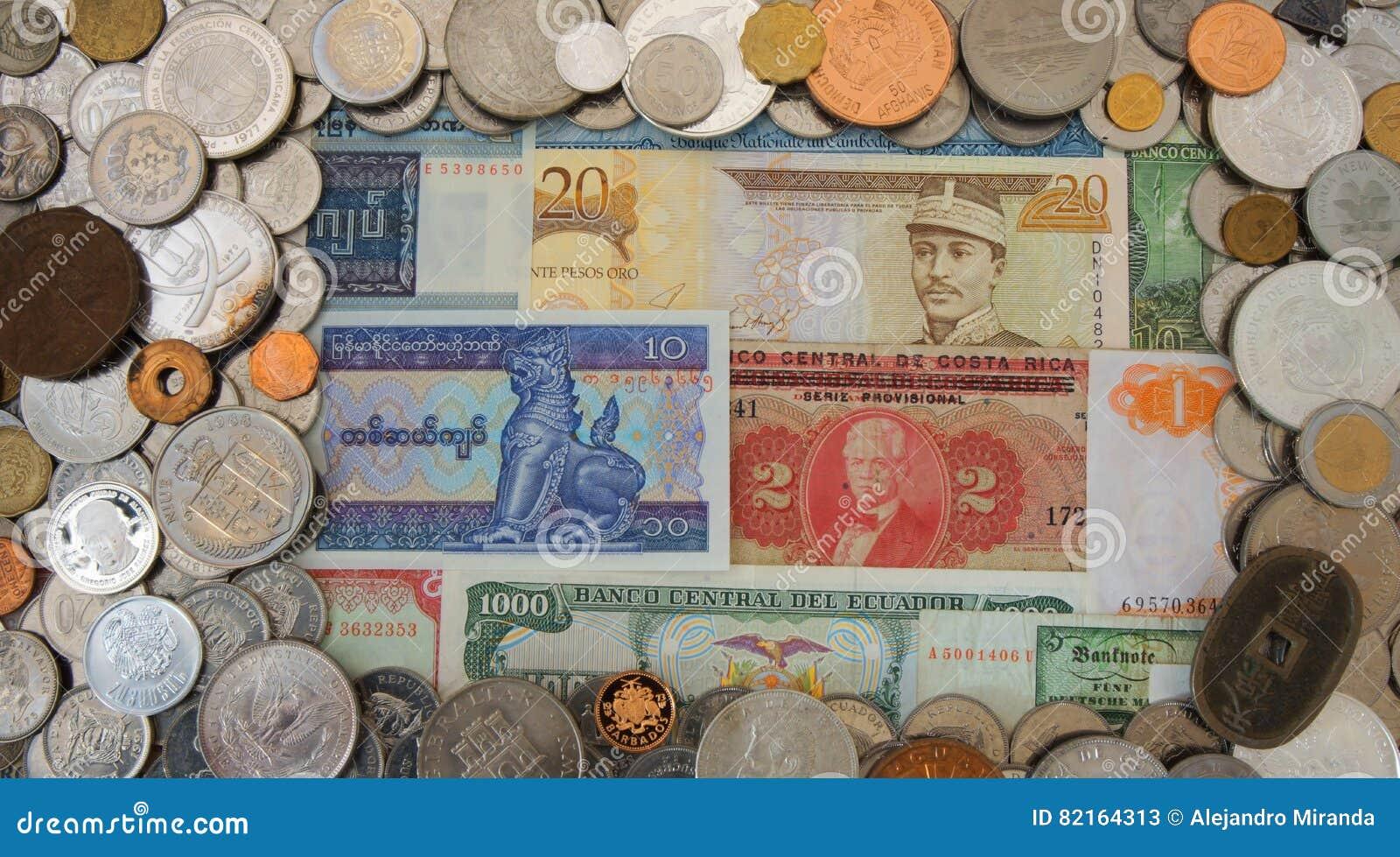 Ram av lotten av mynt av olika länder av världen som är oordnad på gamla sedlar i bakgrunden