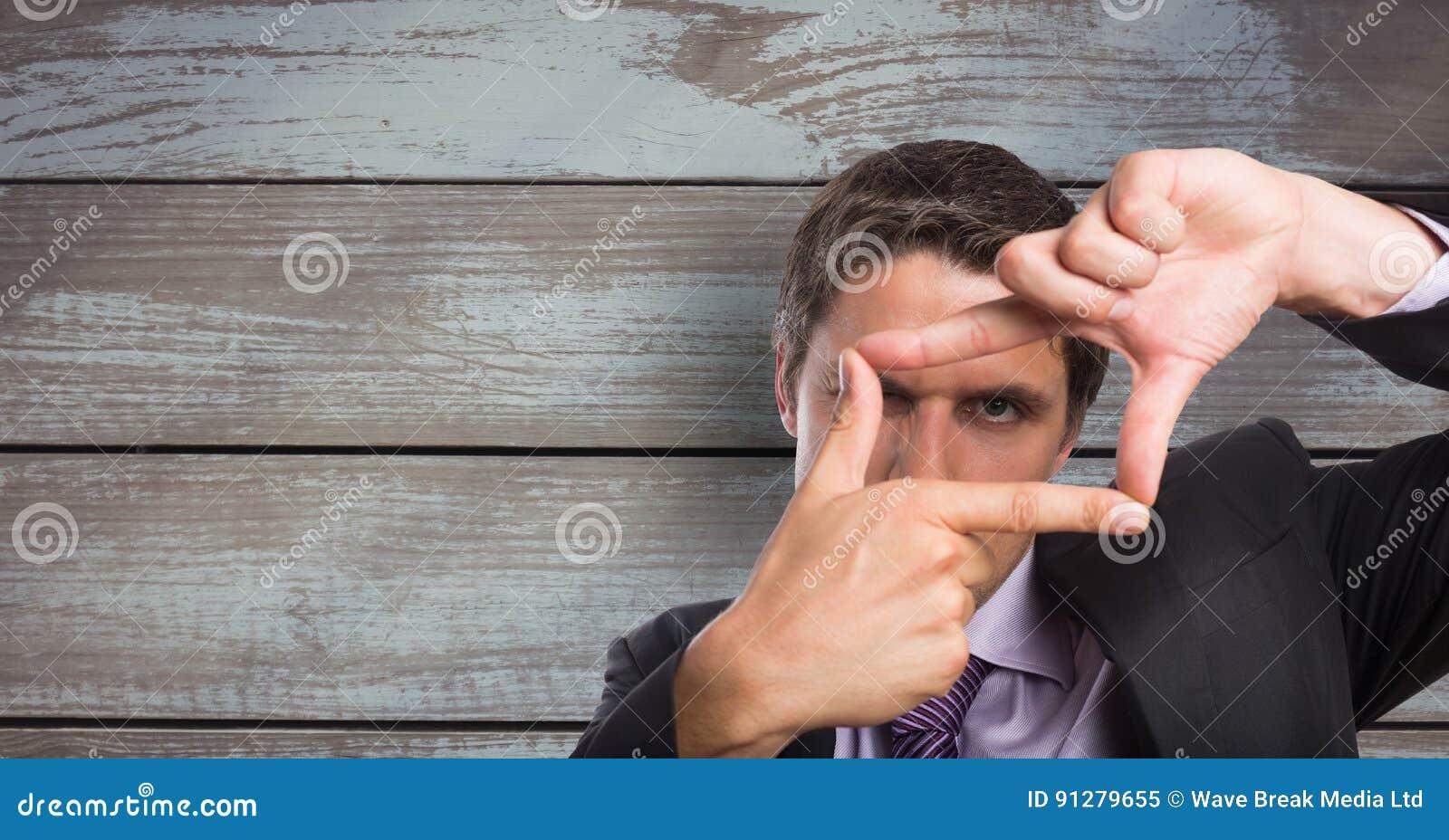 Ram för affärsmandanandefinger mot träväggen