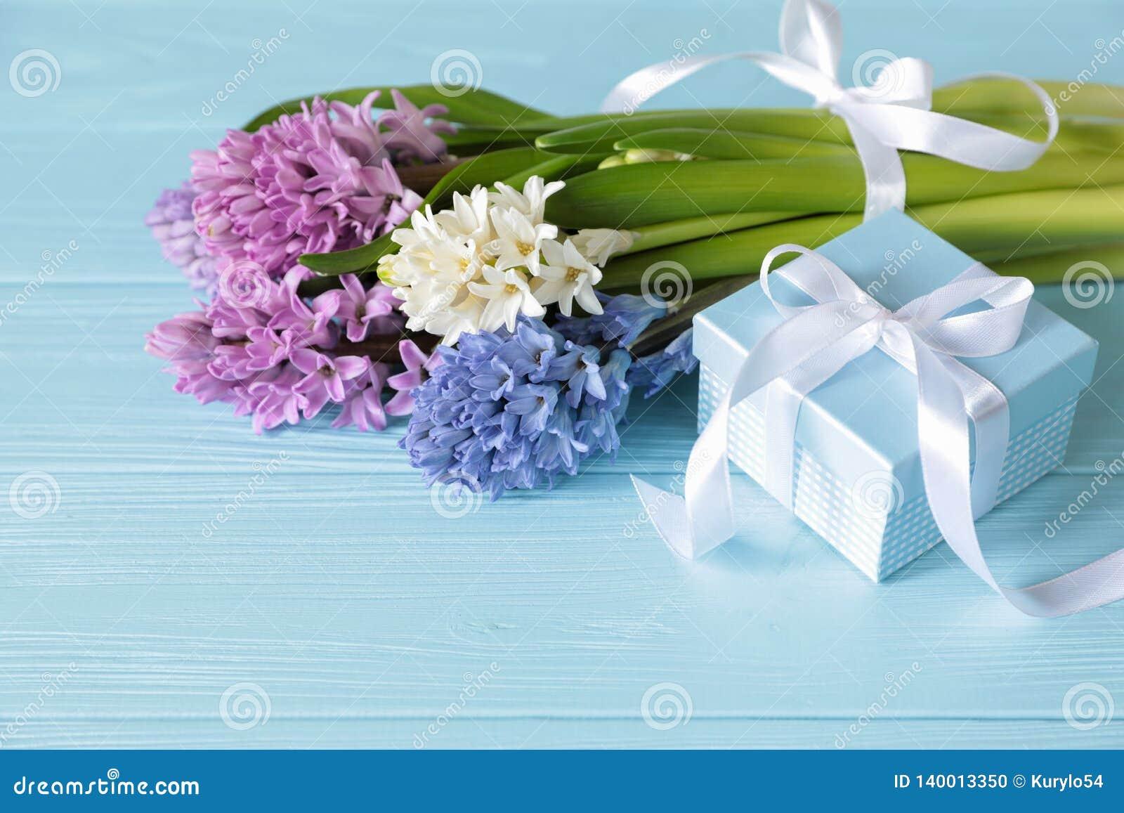 Ramalhete bonito de flores do jacinto no rosa, em cores azuis, brancas, violetas e na caixa de presente azul no fundo de madeira