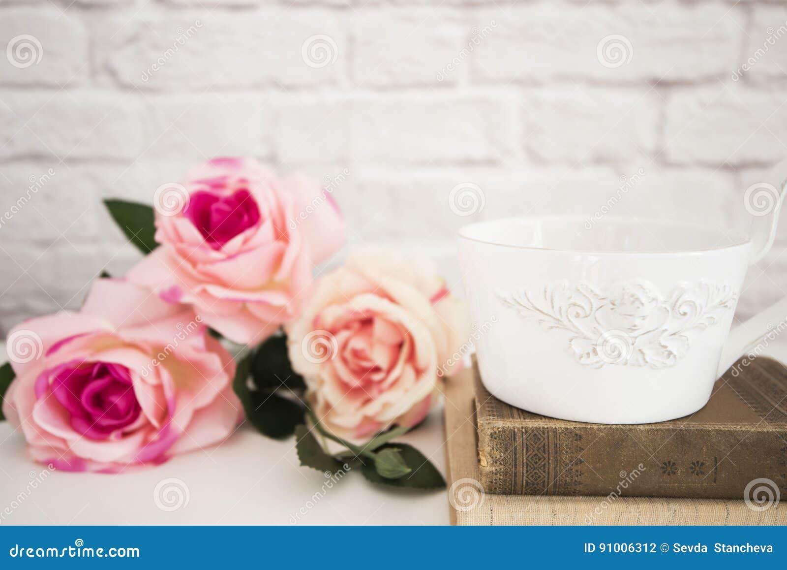 Ramalhete das rosas em uma mesa branca, A grande xícara de café sobre livros velhos, fundo floral romântico do quadro, zombaria d
