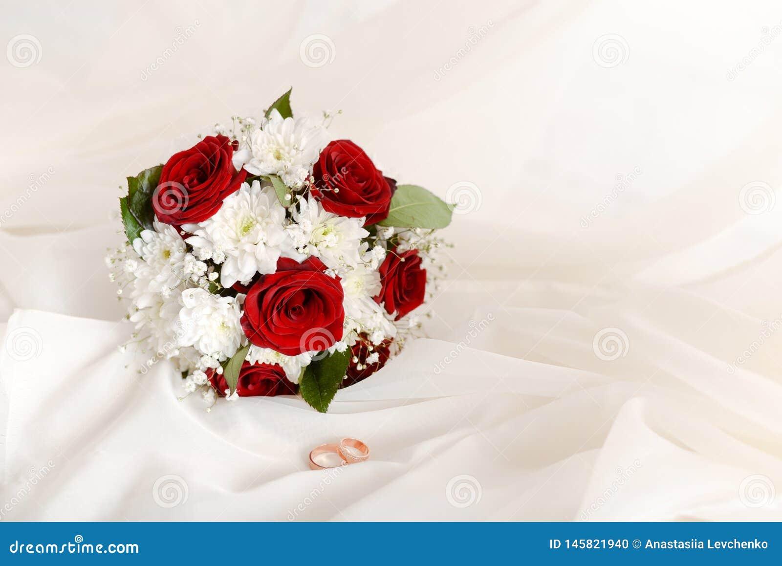 Ramalhete do conceito do casamento de an?is de rosas vermelhas e de ouro do casamento no fundo pastel claro Copie o espa?o