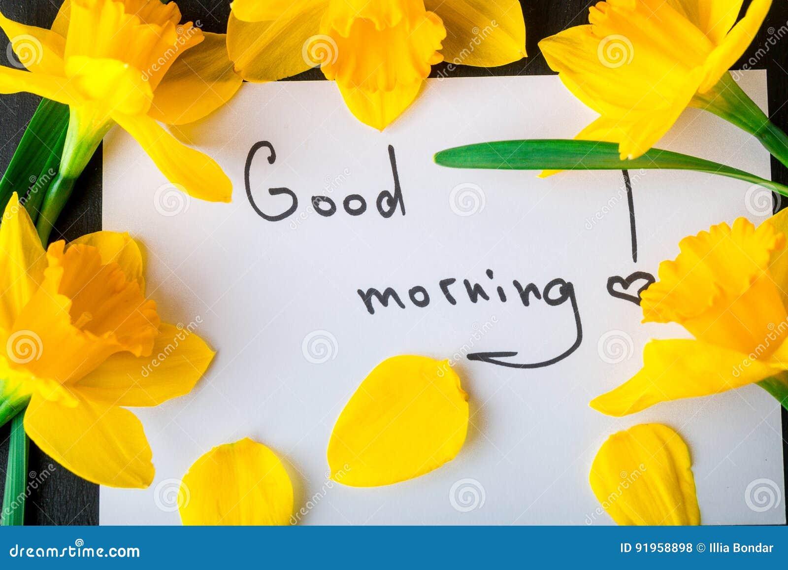 Ramalhete do narciso amarelo perto do cartão com bom dia no fundo preto Vista superior Copie o espaço Dia de mães ou dia das mulh