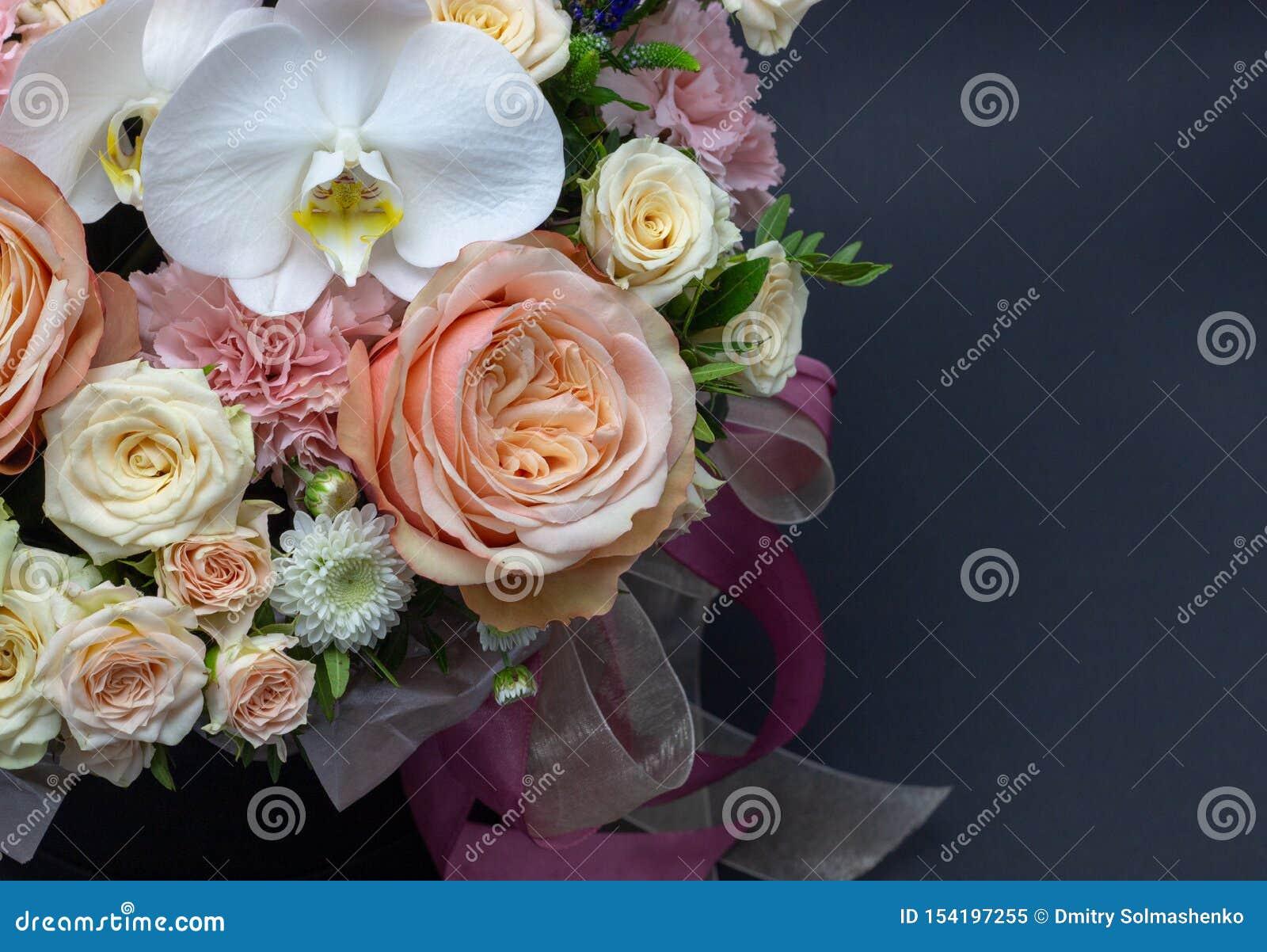 Ramalhete misturado das flores próximas acima do fundo escuro da orquídea branca