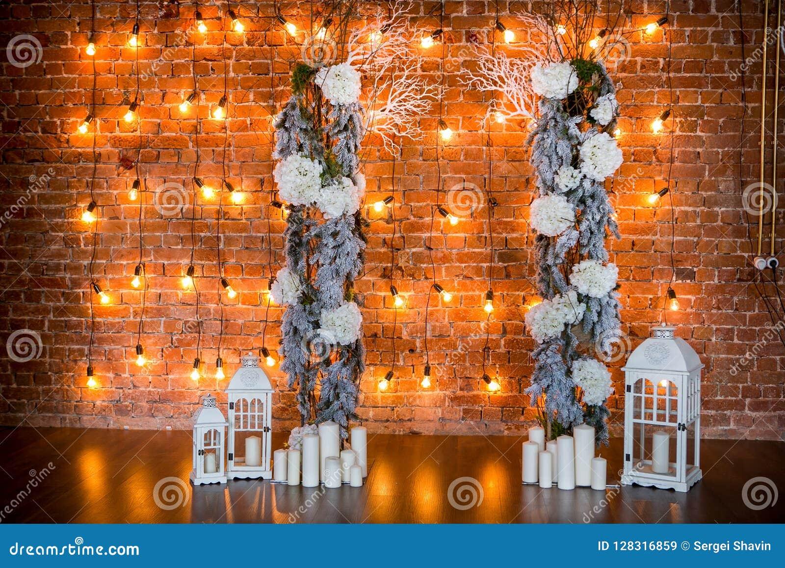 Ramas coníferas con los arbustos de la hortensia, las velas y las bombillas en un fondo del ladrillo