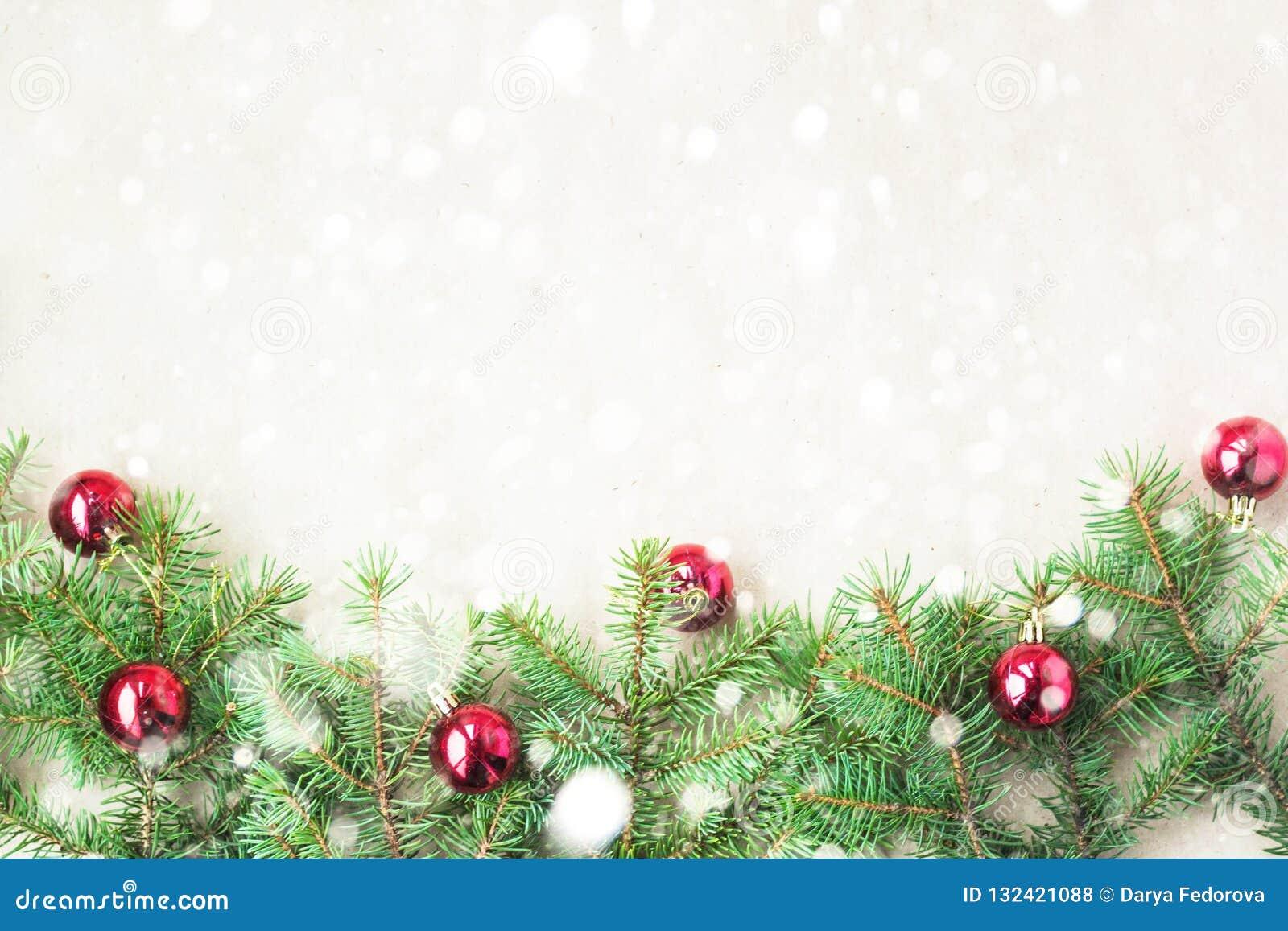 Ramas de árbol de abeto adornadas con las bolas rojas de la Navidad como frontera en un marco rústico del fondo del día de fiesta