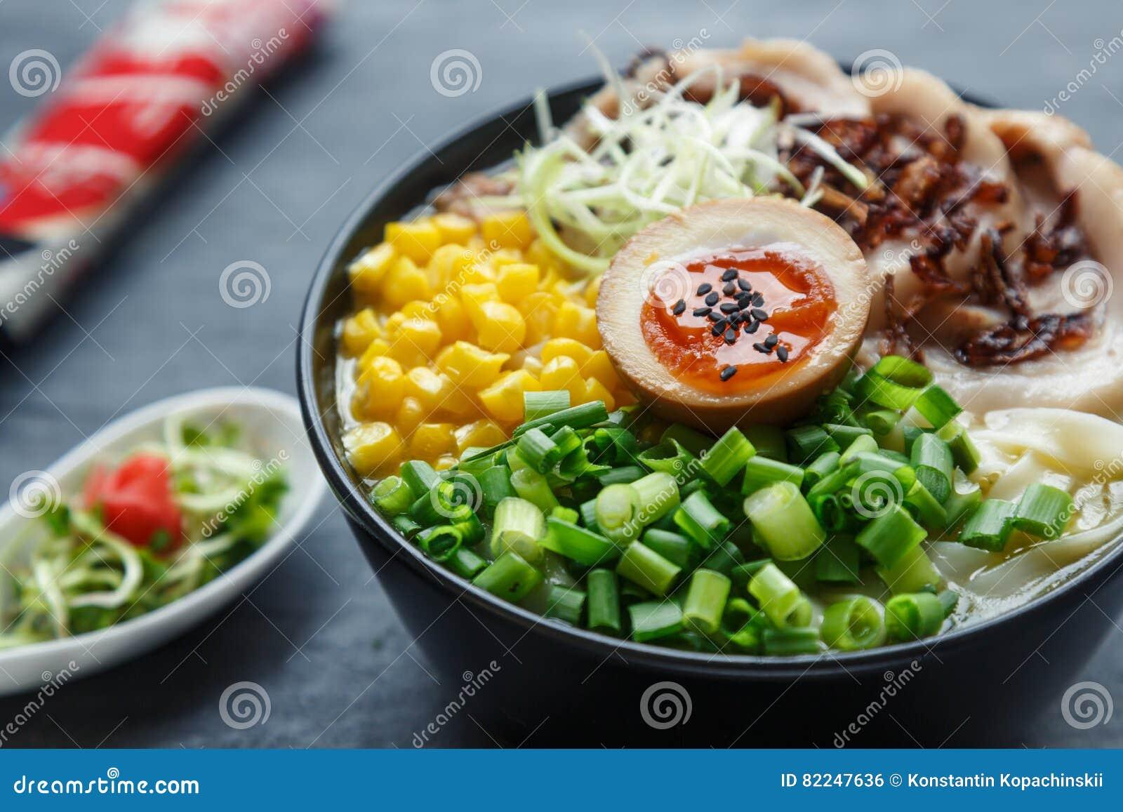 Ramen de Tonkotsu, sopa de macarronete japonesa com barriga de carne de porco, milho, cebola da mola e nitamago na parte superior