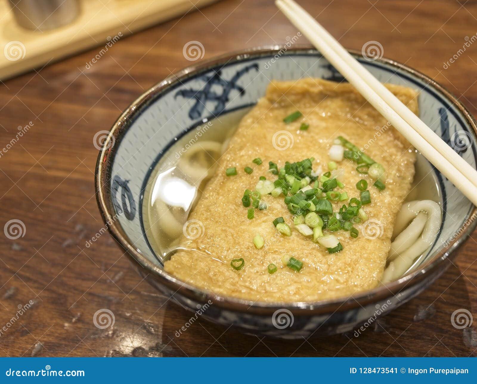 Ramen ou macarronetes japoneses que cobrem com tofu e chalotas fritados na sopa clara