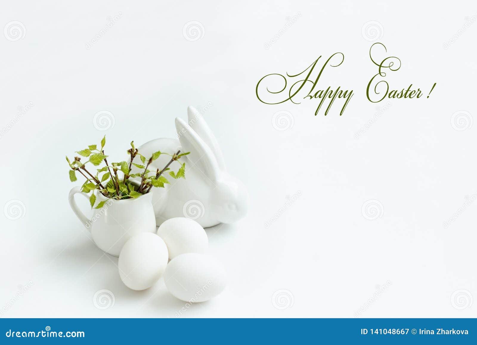 Rami della betulla delle uova di Pasqua, del coniglio e della molla con le giovani foglie su fondo bianco, iscrizione felice di P