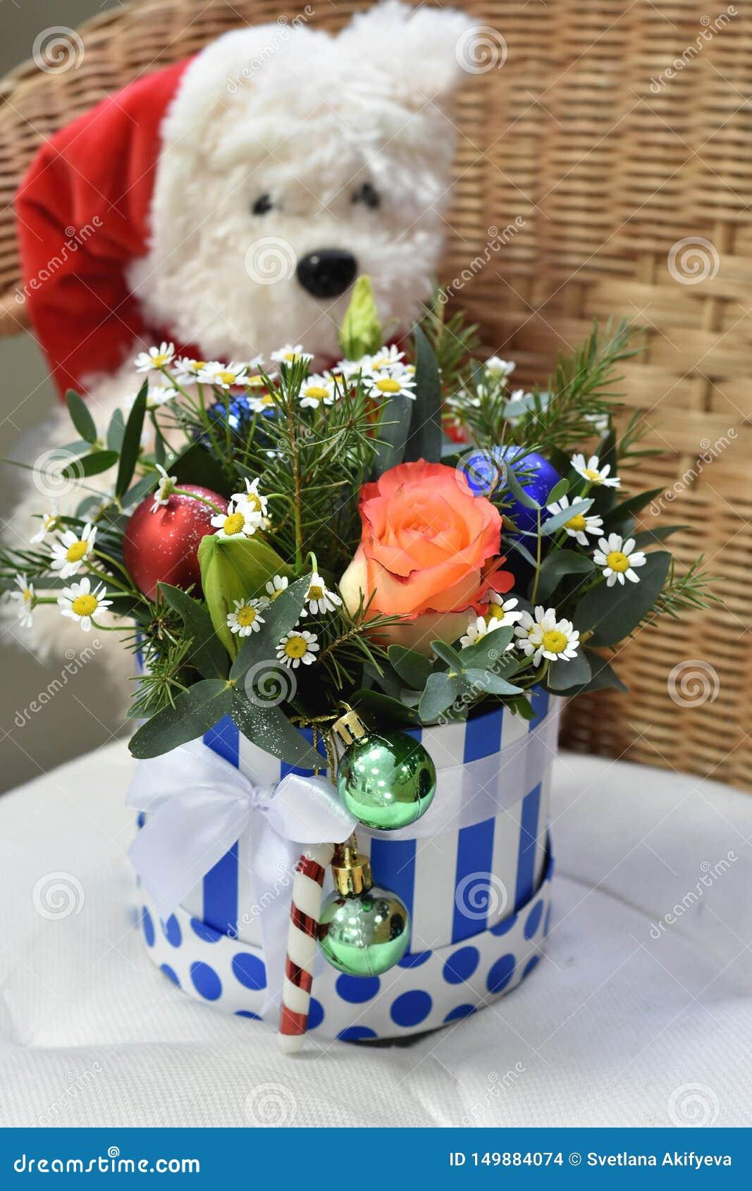 Ramo de árbol de navidad con las decoraciones de la Navidad y las flores preciosas Oso polar del juguete en el fondo