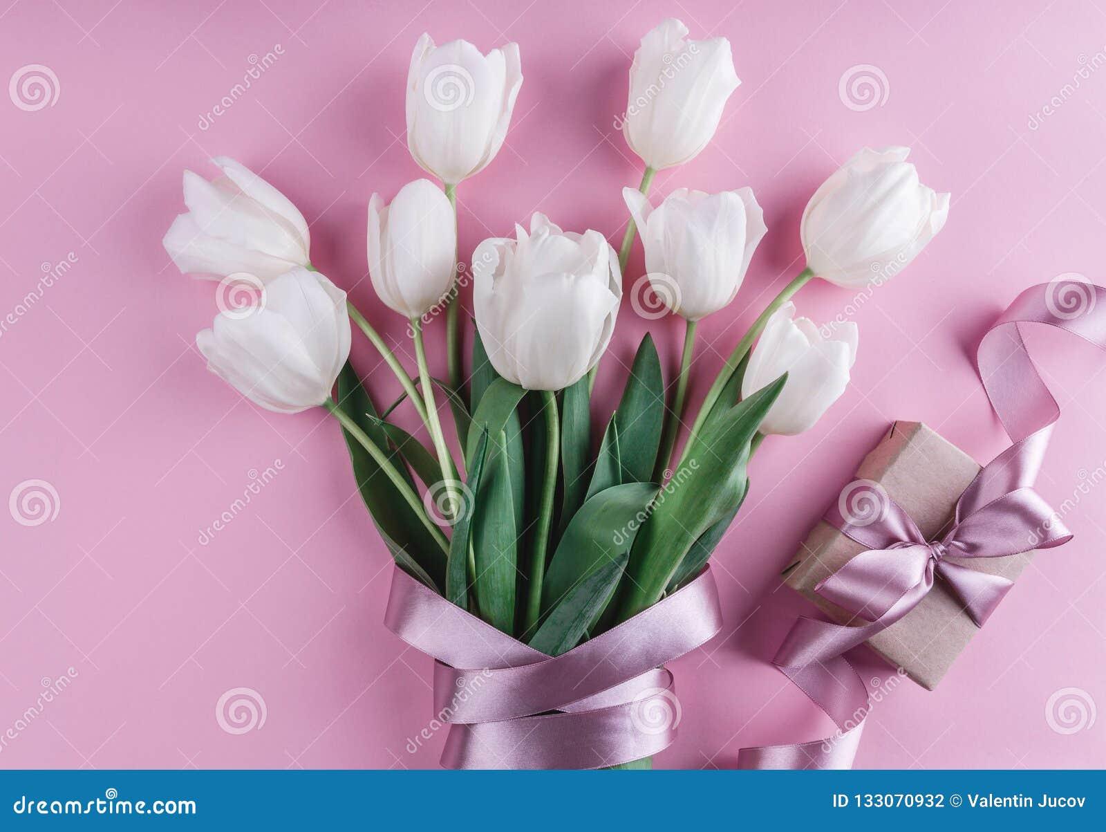 Ramo de flores blancas de los tulipanes con el regalo sobre fondo rosado Tarjeta de felicitación o invitación de la boda