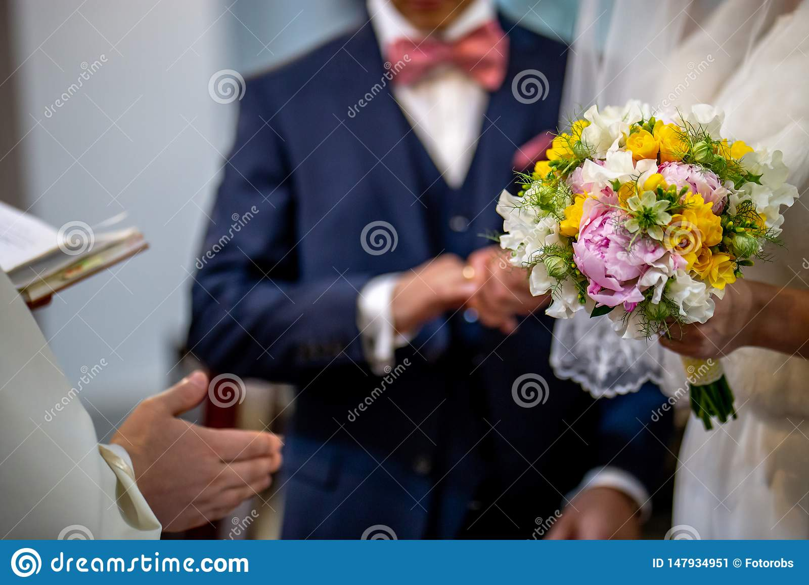 Ramo de flores en la mano de la novia durante la ceremonia de matrimonio