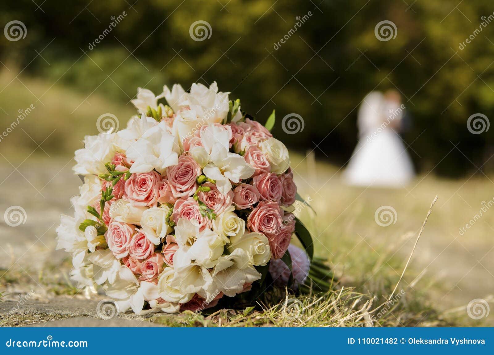 Ramo de la boda en la hierba y los recienes casados