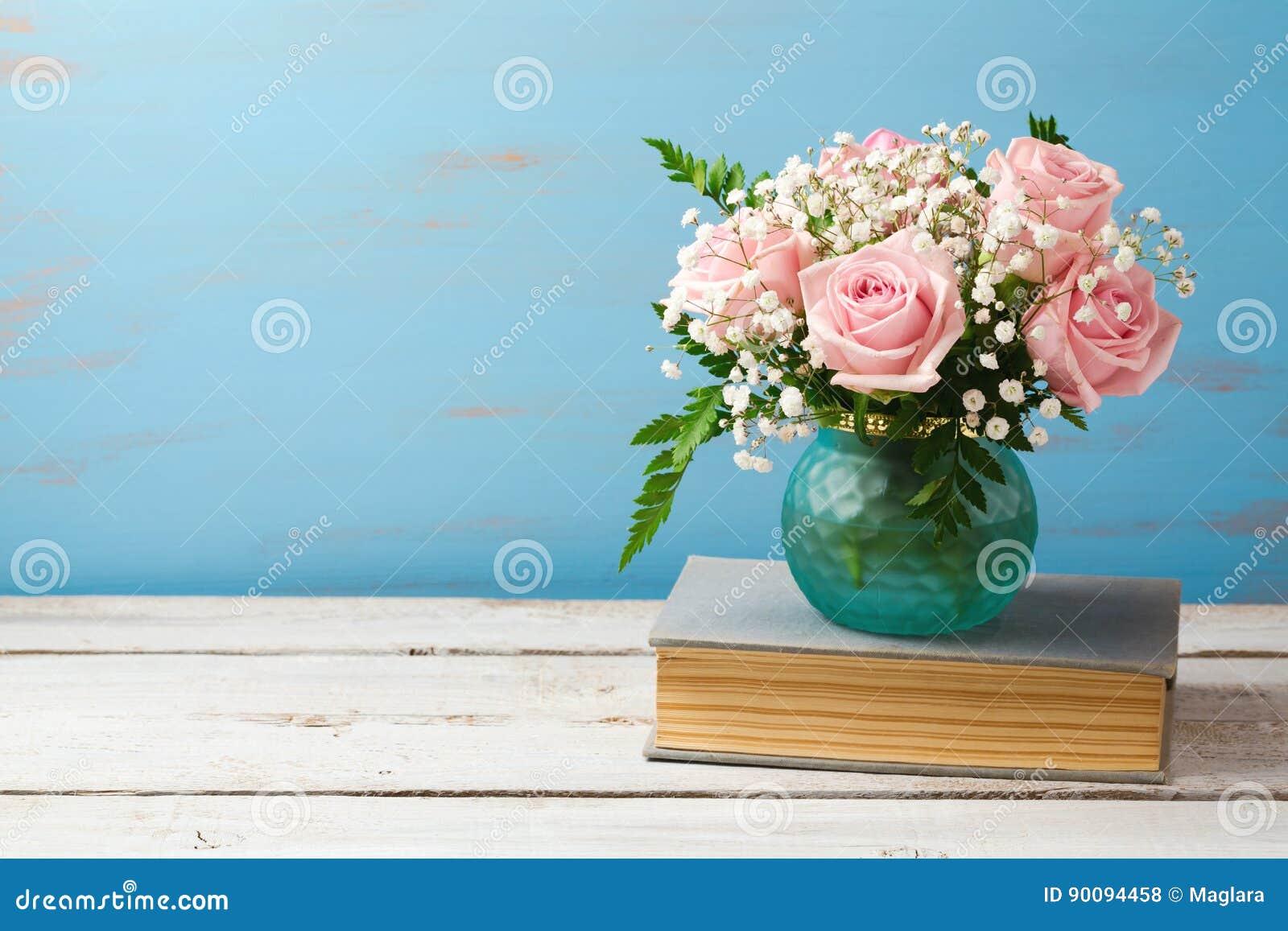 Ramo de la flor de Rose en florero en los libros viejos sobre fondo de madera