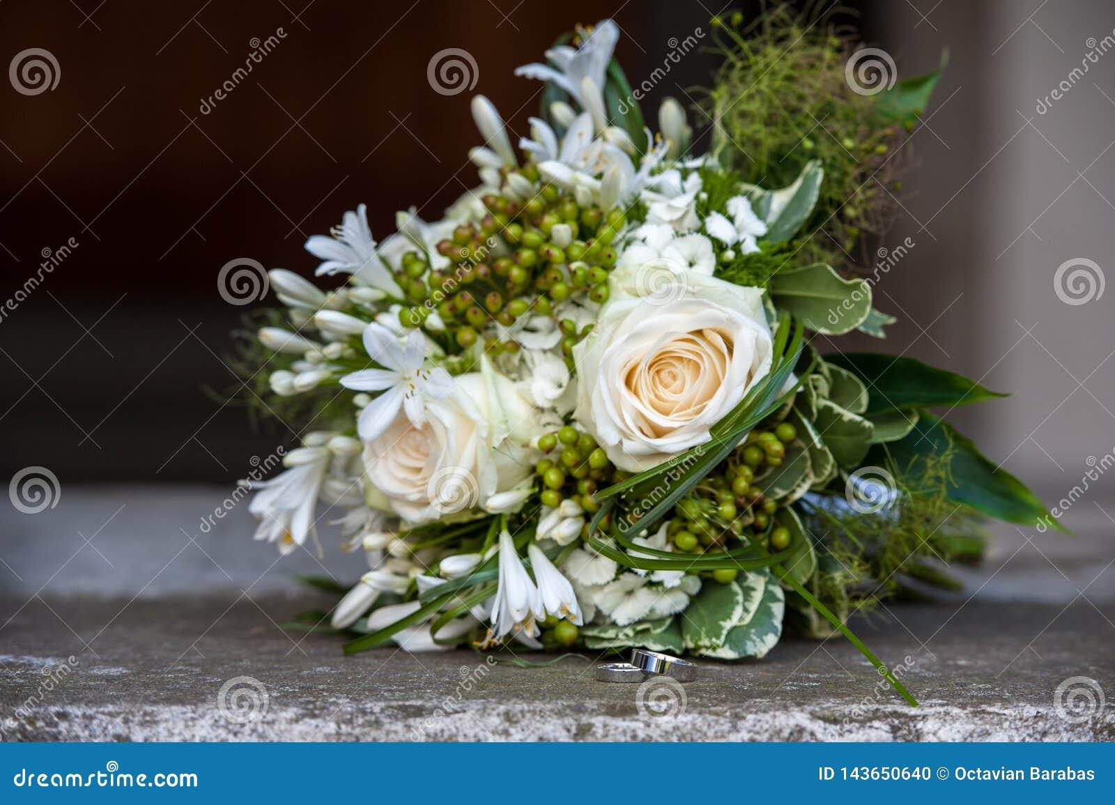 Ramo de la flor y anillos de bodas en las escaleras de la iglesia