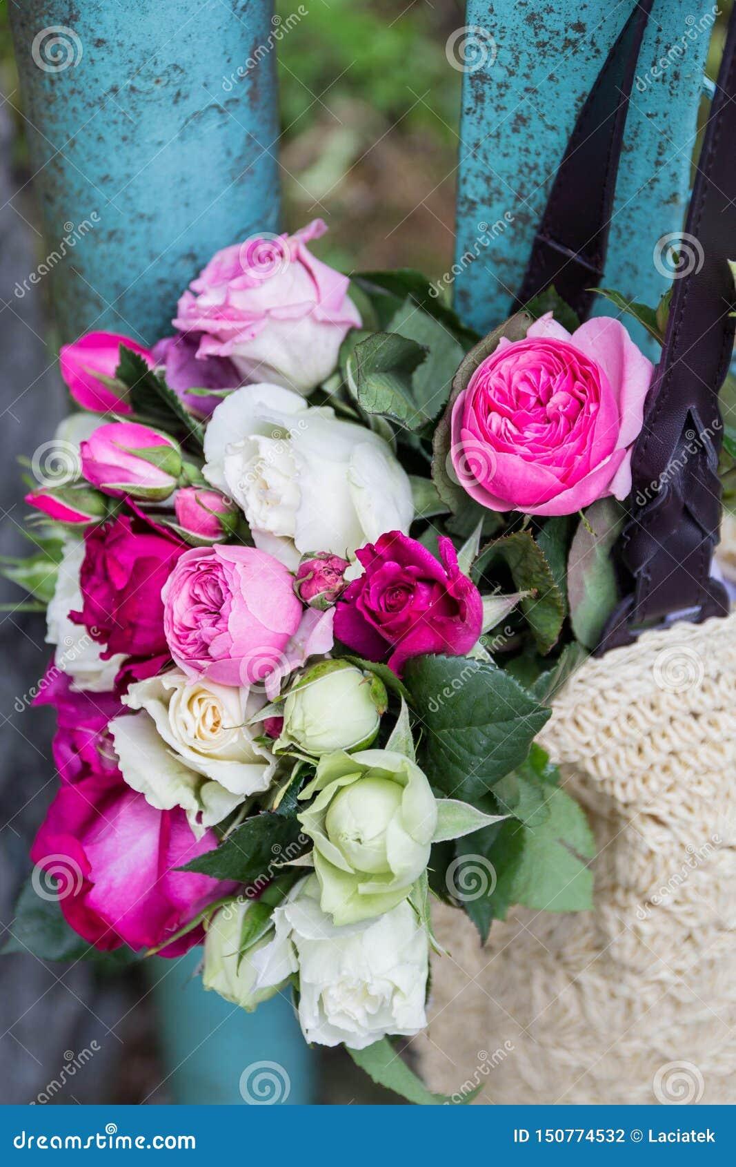 Ramo de rosas inglesas fragantes del rosa y blancas en un bolso de la rafia que cuelga en la cerca