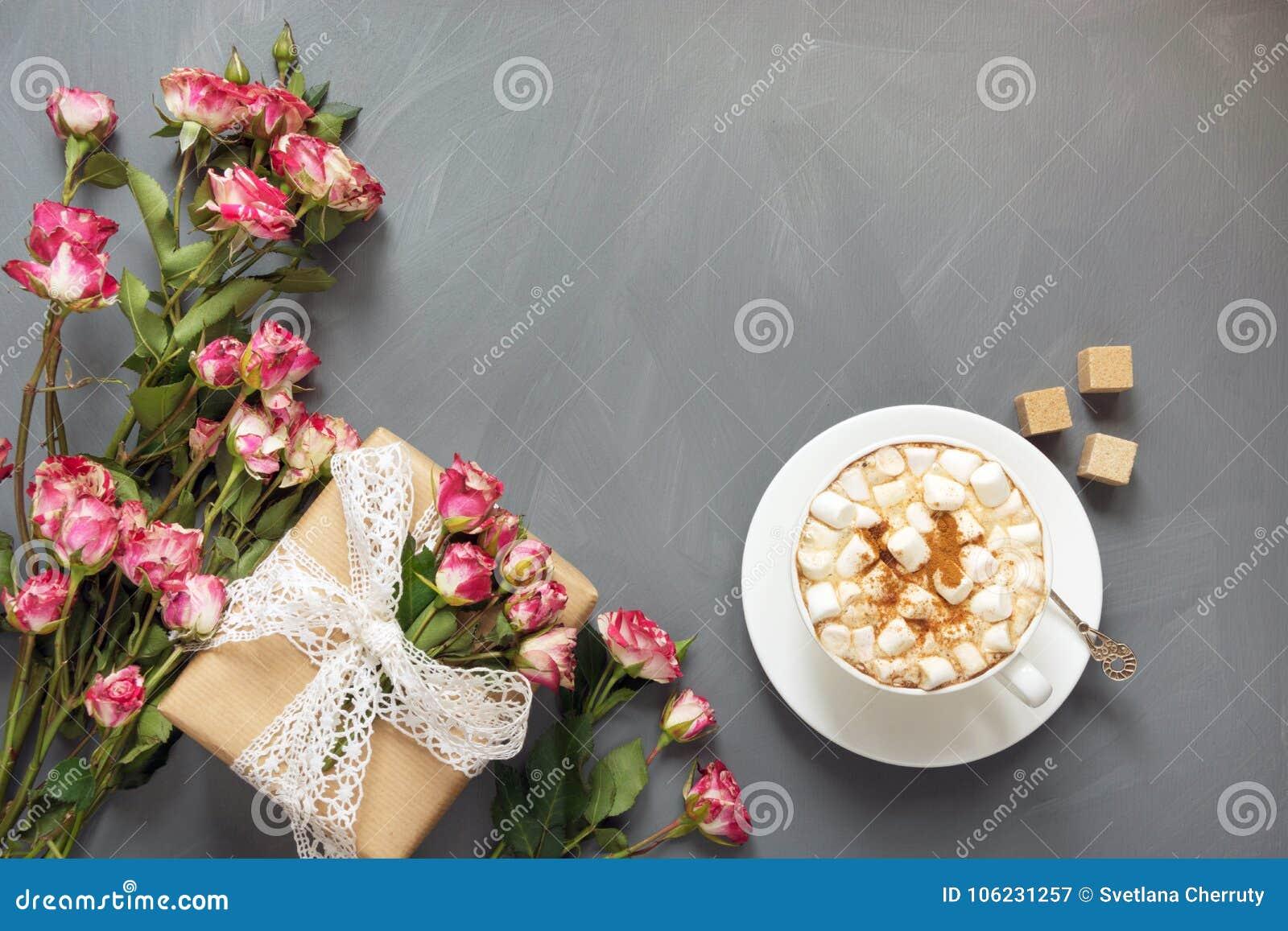 Ramo de rosas rosadas del arbusto, de regalo femenino y de taza de café en el fondo elegante lamentable, punto de visión superior