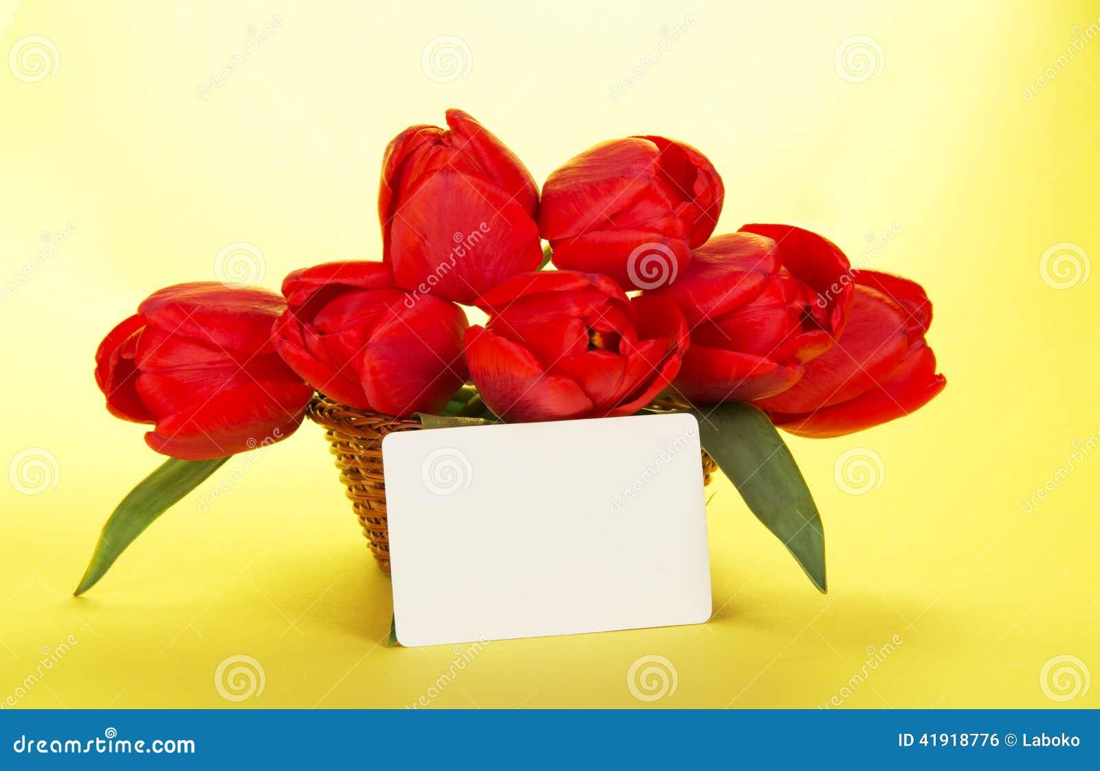 Ramo de tulipanes rojos en cesta y la tarjeta blanca