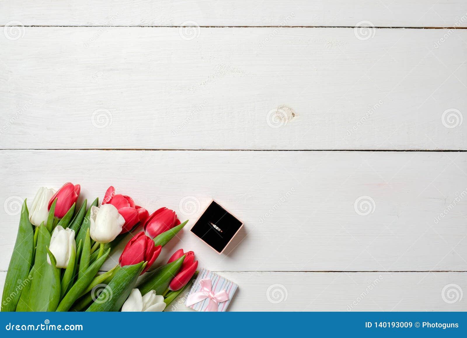 Ramo de tulipanes y de caja del anillo en el fondo de madera blanco Propuesta de matrimonio, tarjeta de la invitación de la boda