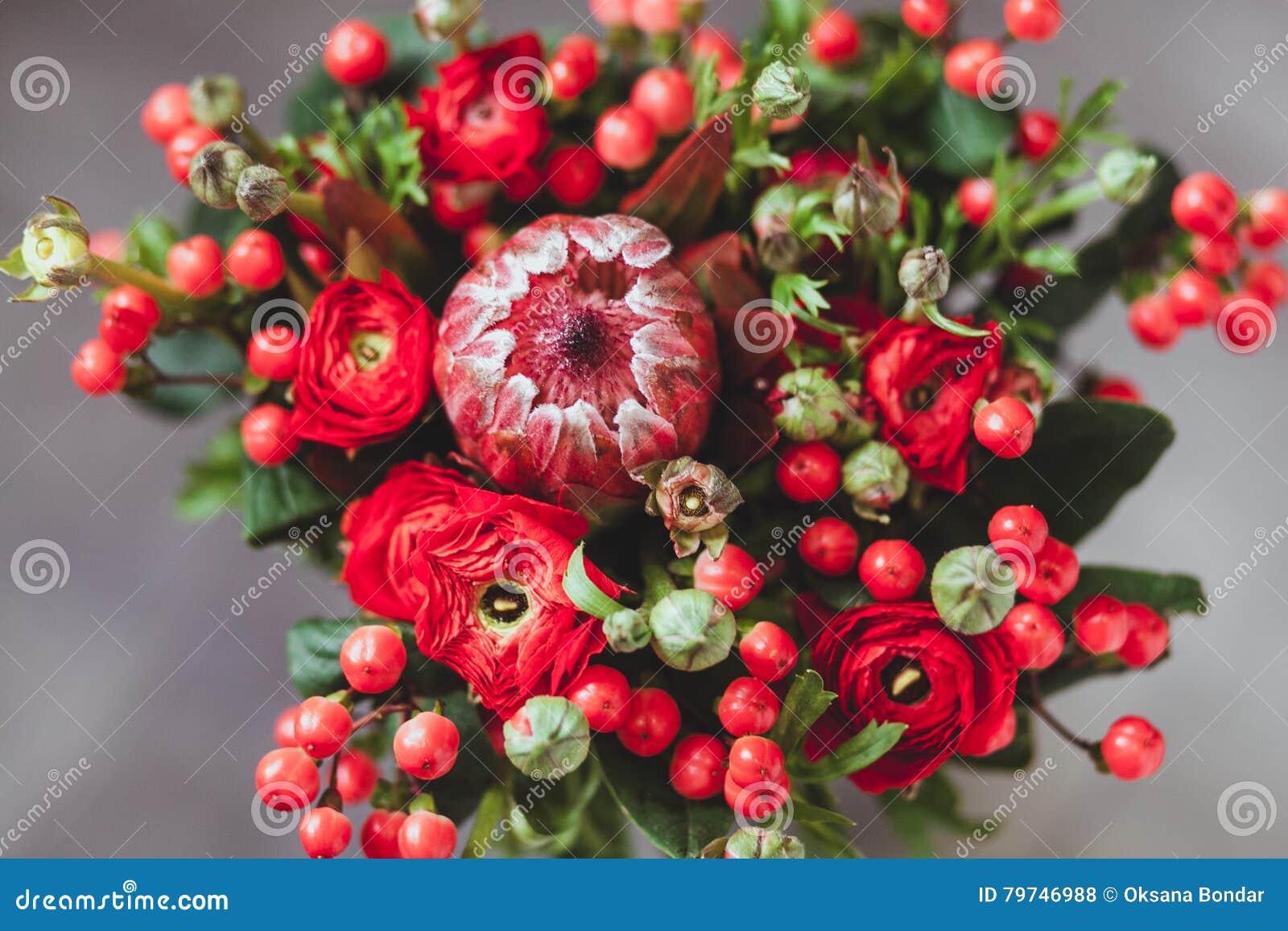Ramo del Protea y de los ranúnculos en un fondo gris blured