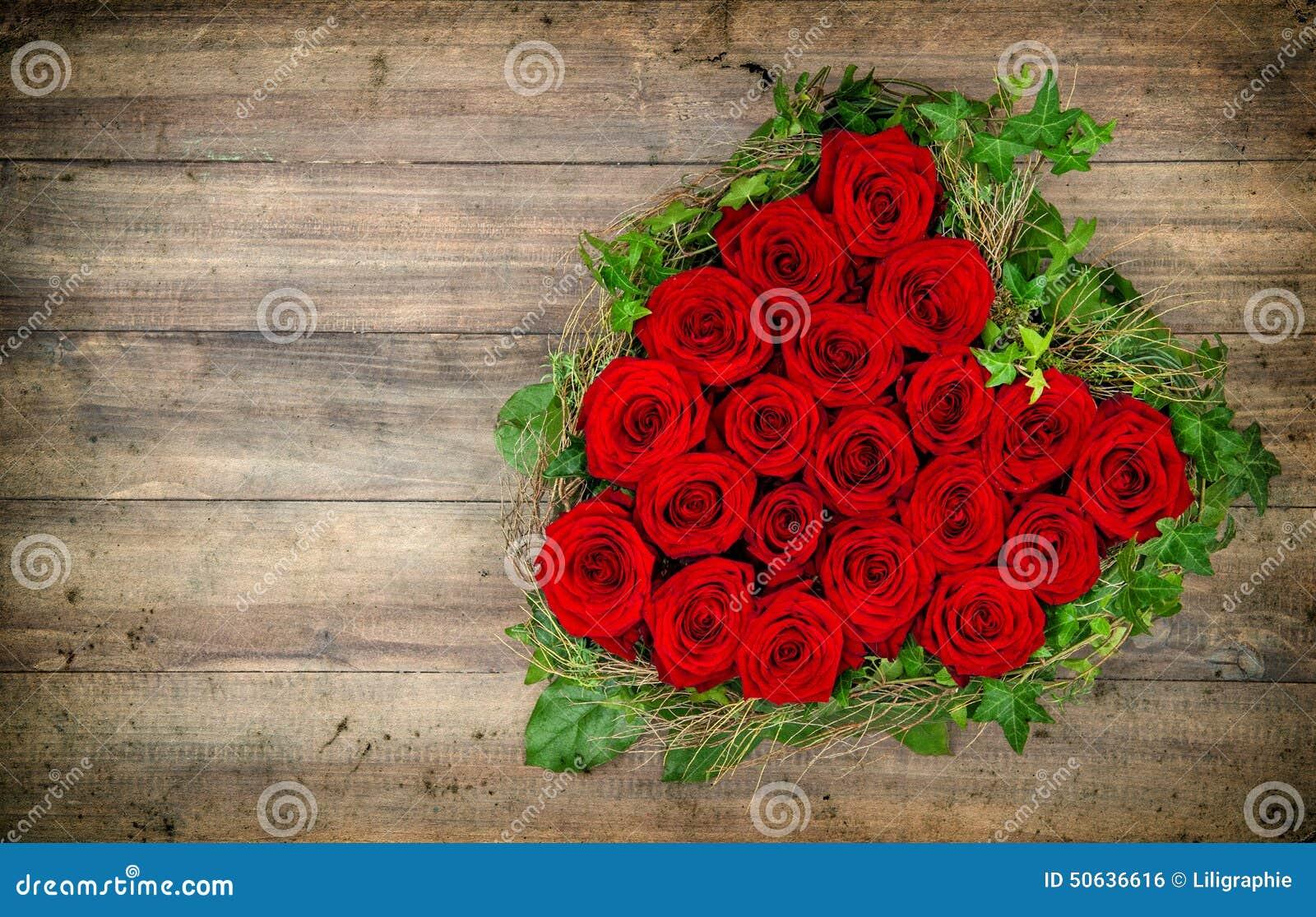 Ramo en forma de corazón de las rosas rojas en fondo de madera valentines