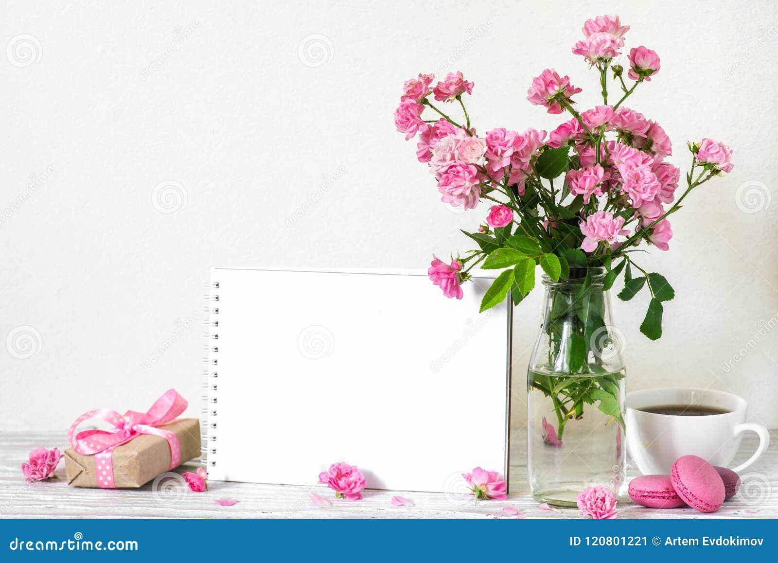 Ramo hermoso de flores rosadas de las rosas, de taza de café, de macarrones, de caja de regalo y de tarjeta de felicitación blanc