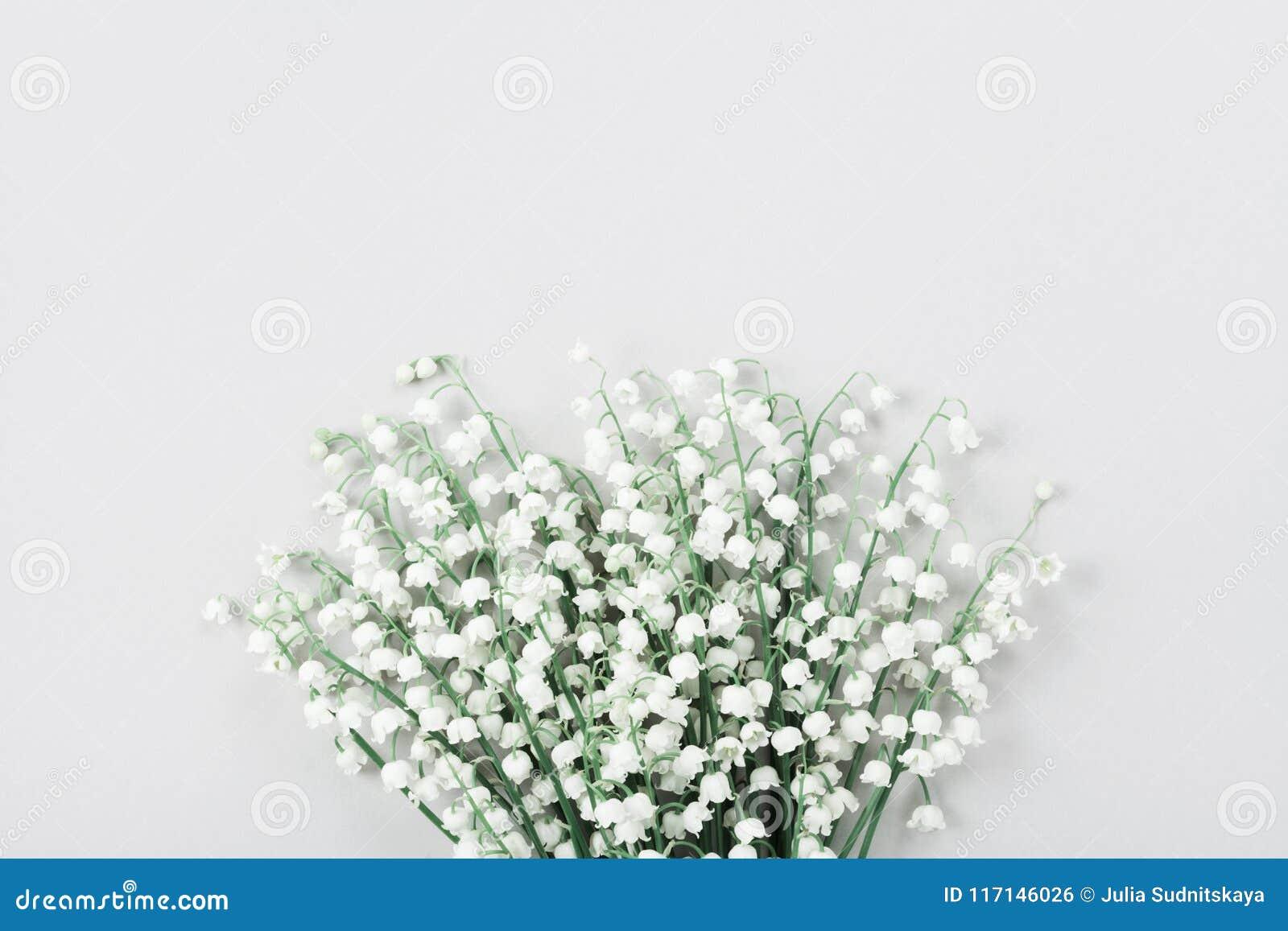 Ramo hermoso de lirio de los valles de las flores en la tabla en colores pastel desde arriba Composición mínima y estilo plano de
