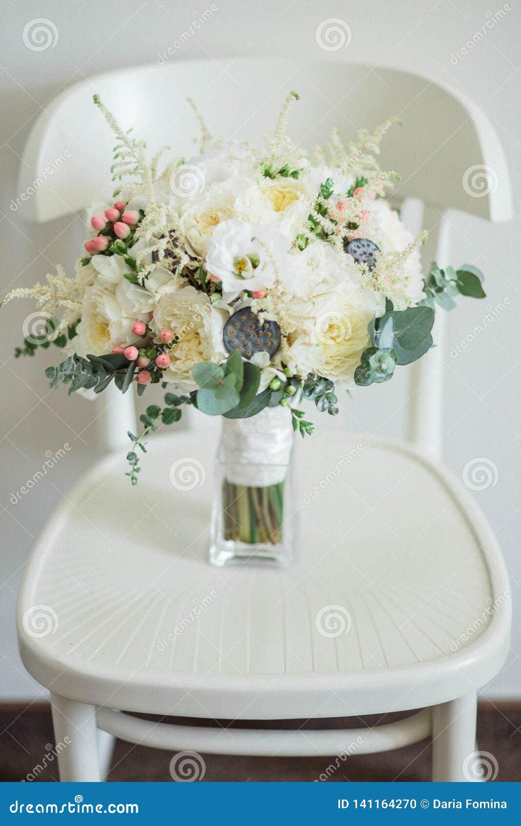 Ramo nupcial Hermoso de las flores blancas y del verdor, en silla de madera del vintage
