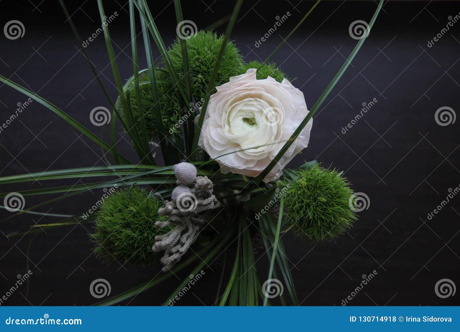 Ramo oscuro hermoso con el clavel mullido verde, un ranúnculo grande apacible y la hierba en fondo de madera negro