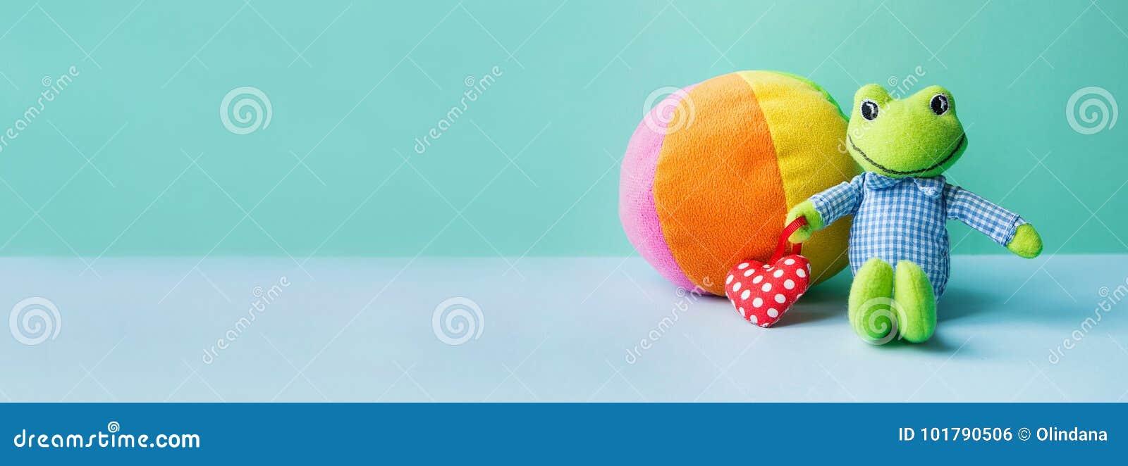 Rana dei giocattoli dei bambini piccola che tiene la palla molle del tessuto multicolore rosso del cuore sul fondo di verde blu O