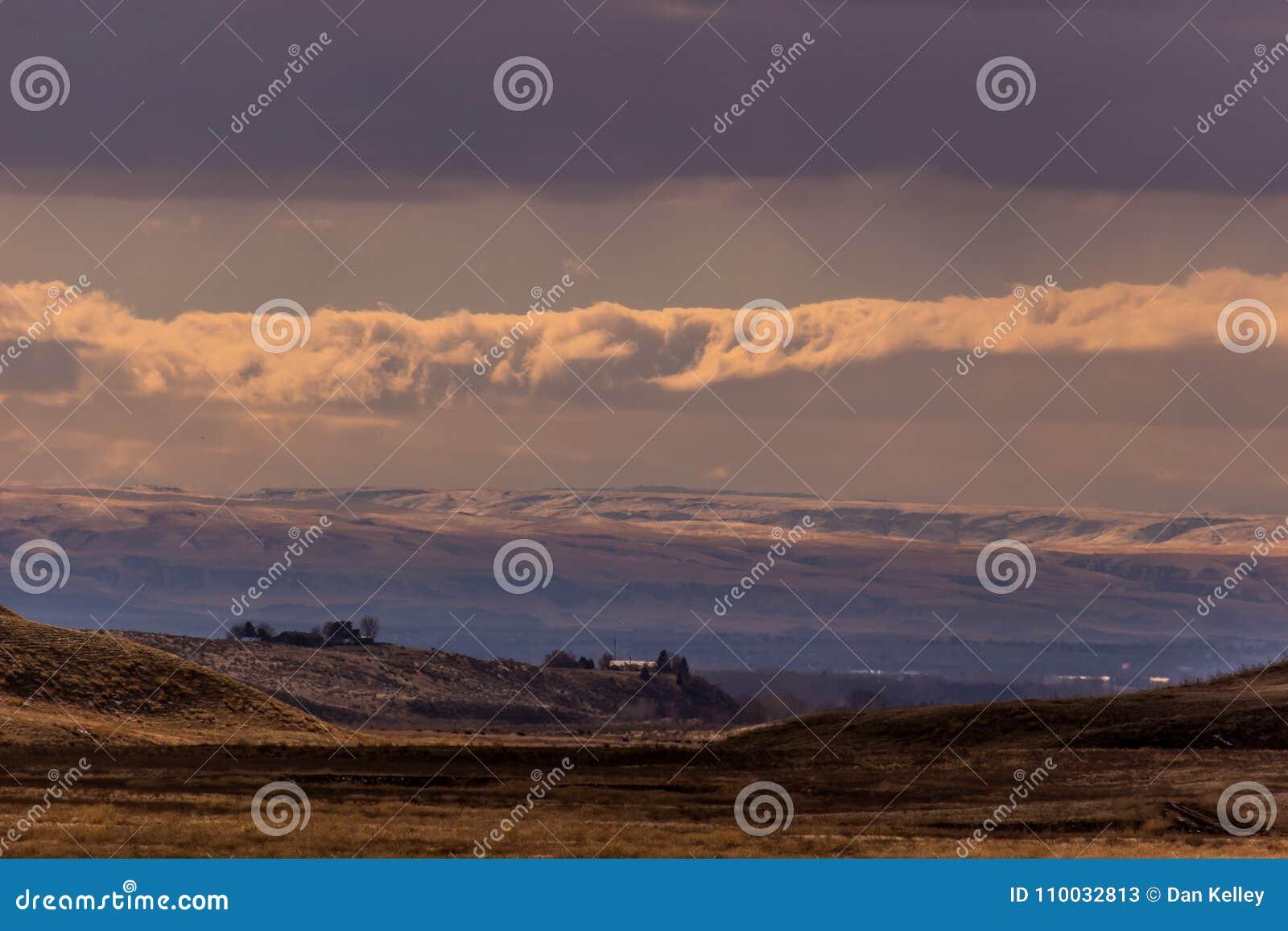 Ranch de l Idaho au coucher du soleil après une neige légère sous le ciel bleu et les nuages cassés