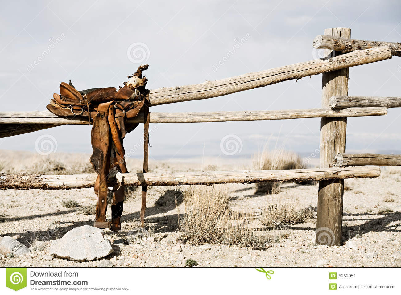 Ranch scene - saddle on rural fence, vintage worn saddle in the dry ...