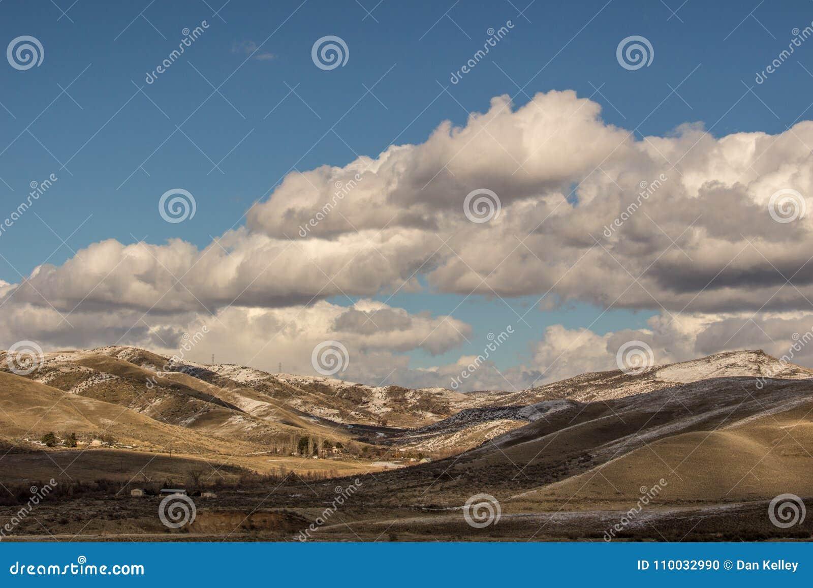 Rancho de las colinas del pie de Idaho después de una nieve ligera debajo del cielo azul y de las nubes quebradas