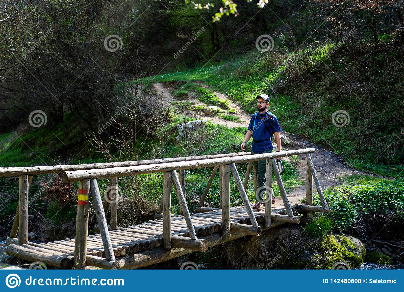 Randonneur croisant le pont en bois dehors