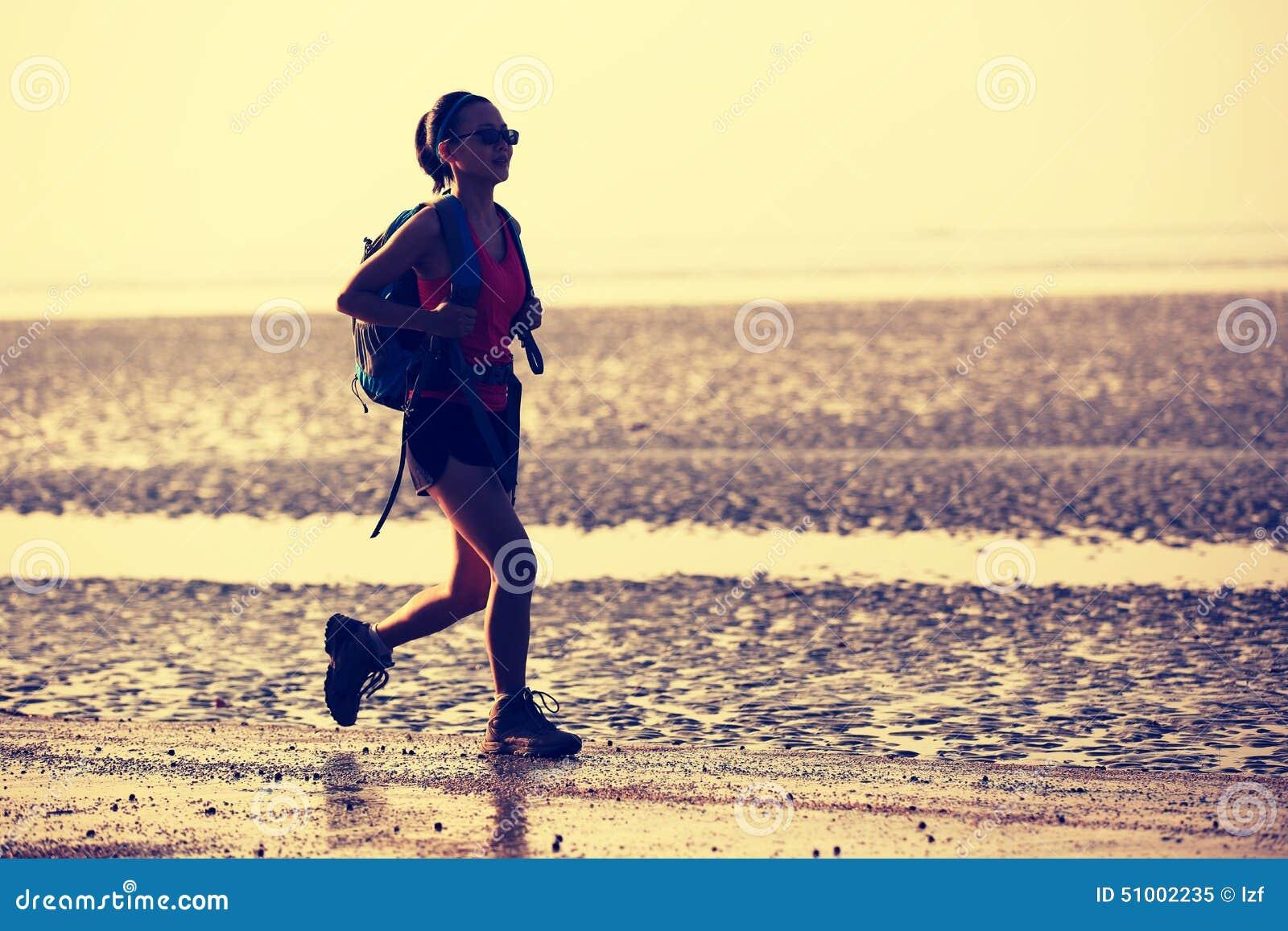 Randonneur de femme trimardant sur la plage de lever de soleil