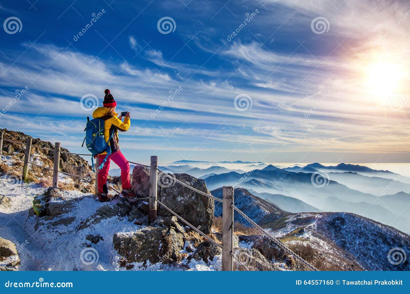 Randonneur de jeune femme prenant la photo avec le smartphone sur la crête de montagnes