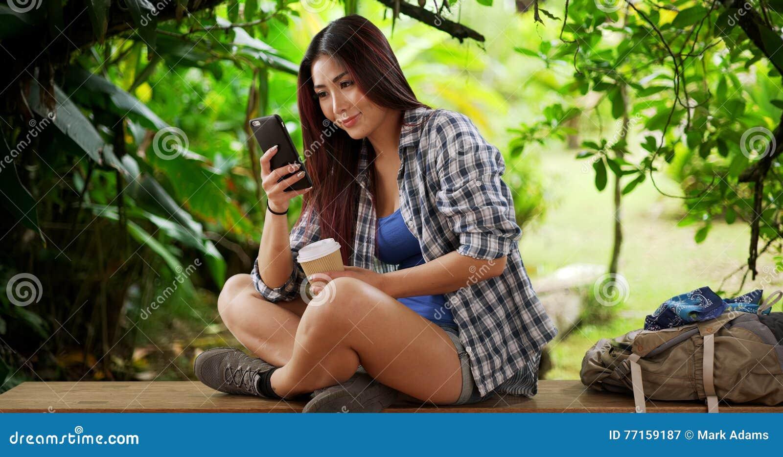Randonneur japonais de femme faisant une pause sur un banc voisin