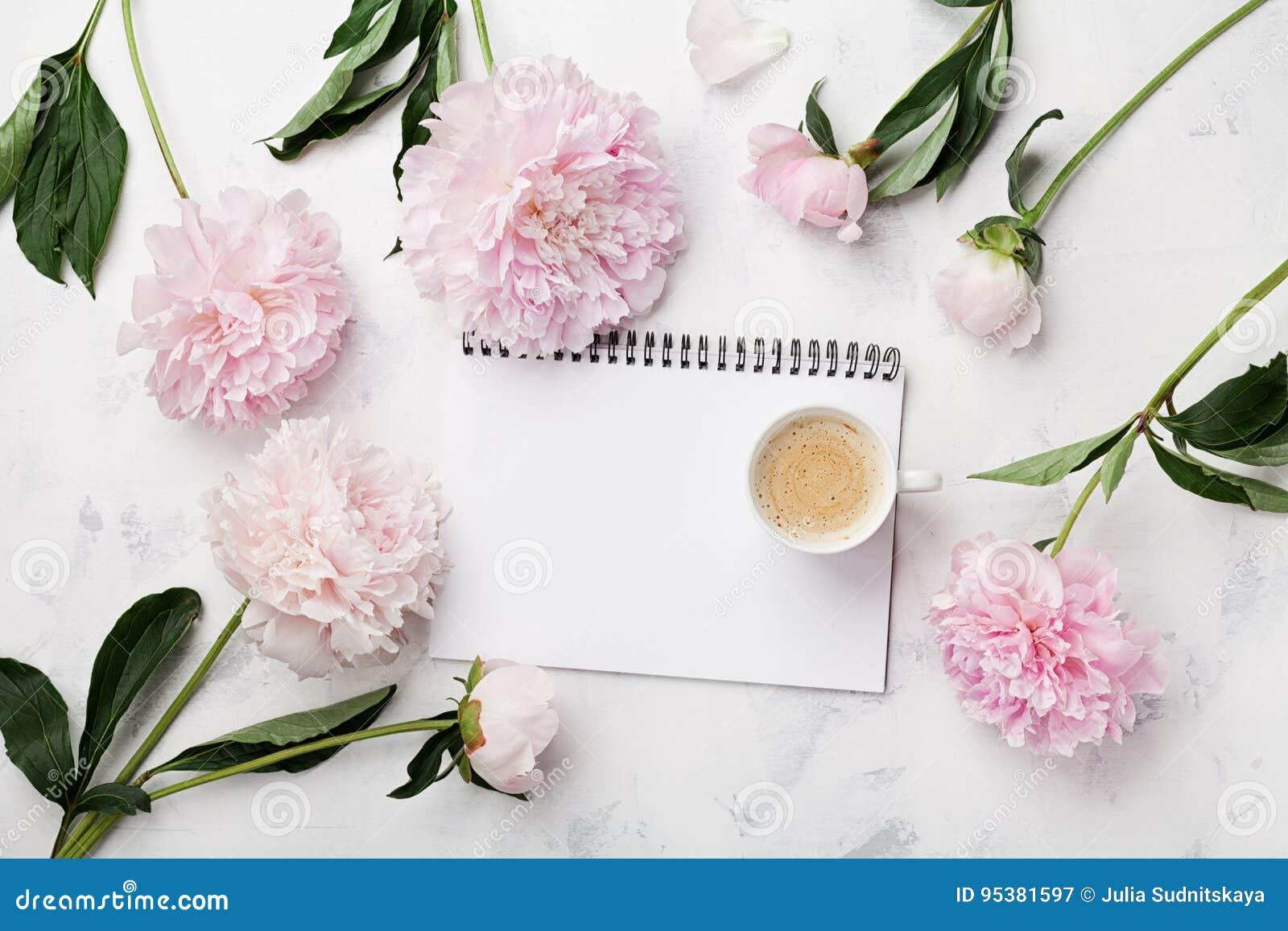 Ranek filiżanka dla śniadania, pusty notatnik i menchii peoni kwiaty na bielu kamienia stołowym odgórnym widoku w mieszkaniu, kła