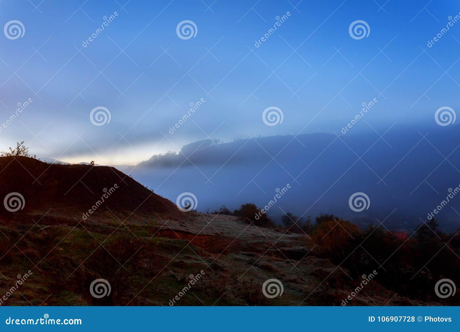Ranek mgła na zbocze łąkowej pobliskiej górskiej wiosce przy nocą w księżyc świetle