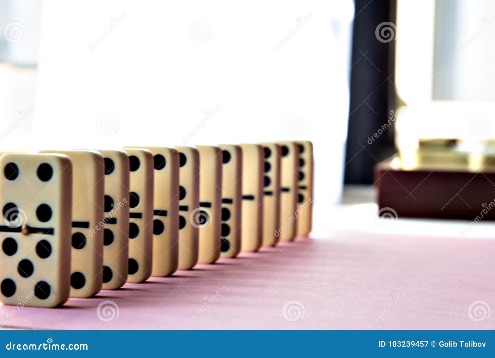 Rangée de domino sur le fond rose