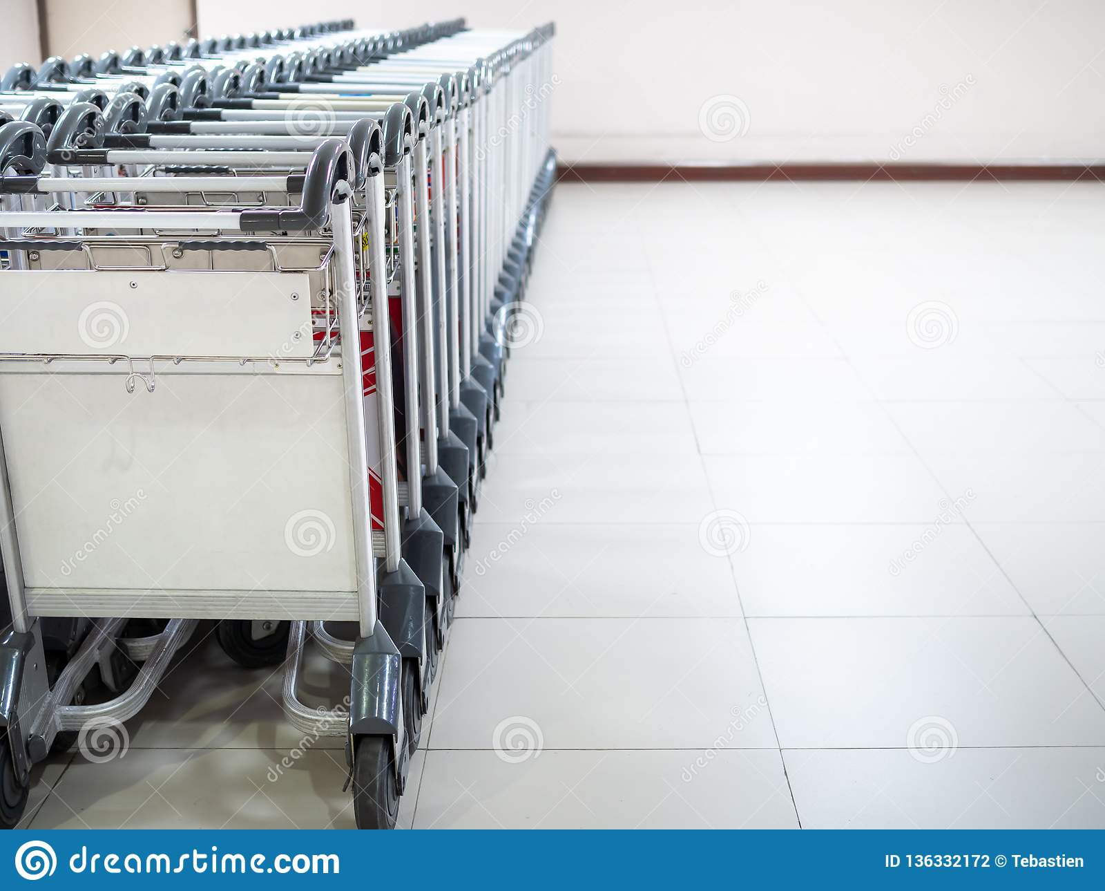 Rangée des chariots de bagage d aéroport dans le terminal d aéroport