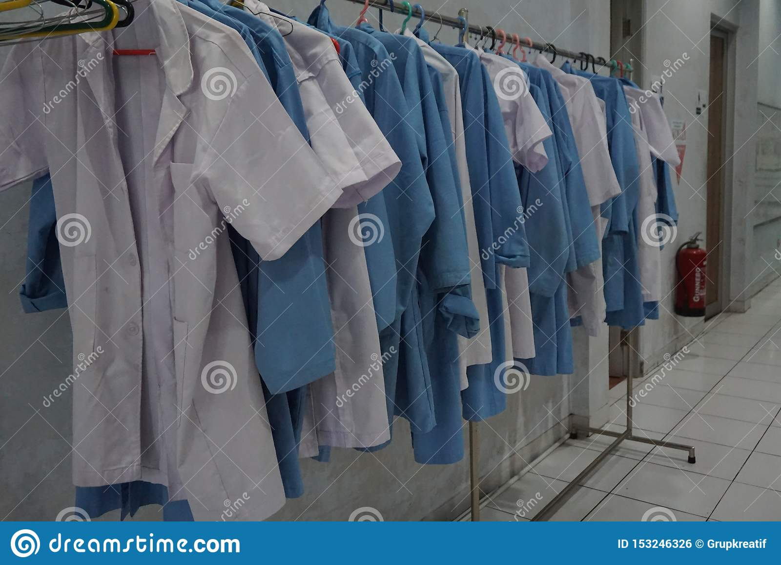 Rangée du manteau blanc et bleu de laboratoire