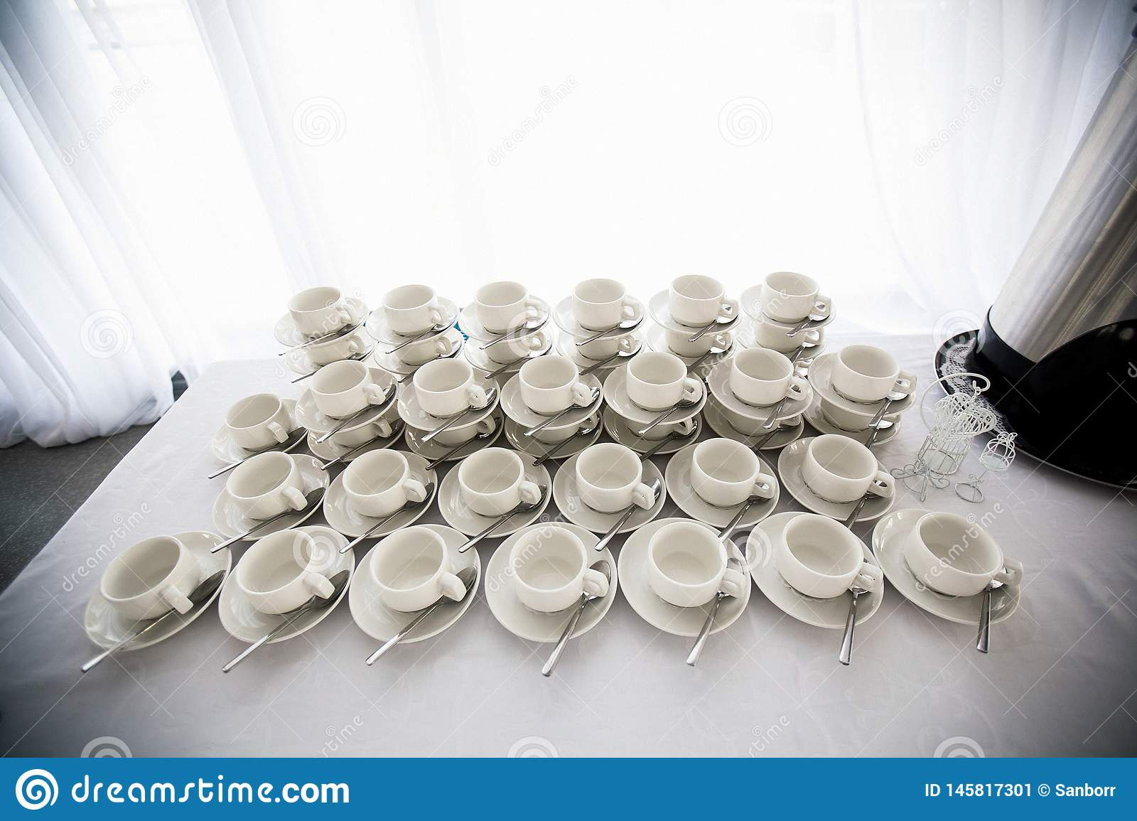 A range of traditional clean empty ceramic coffee cups on the table in the restaurant. Lots of white cups on saucers for serving